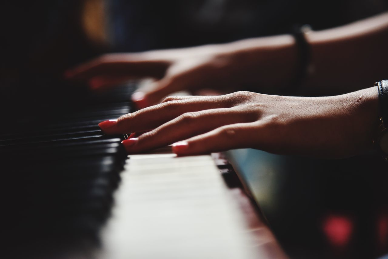 Close-Up Of Hands Playing The Piano
