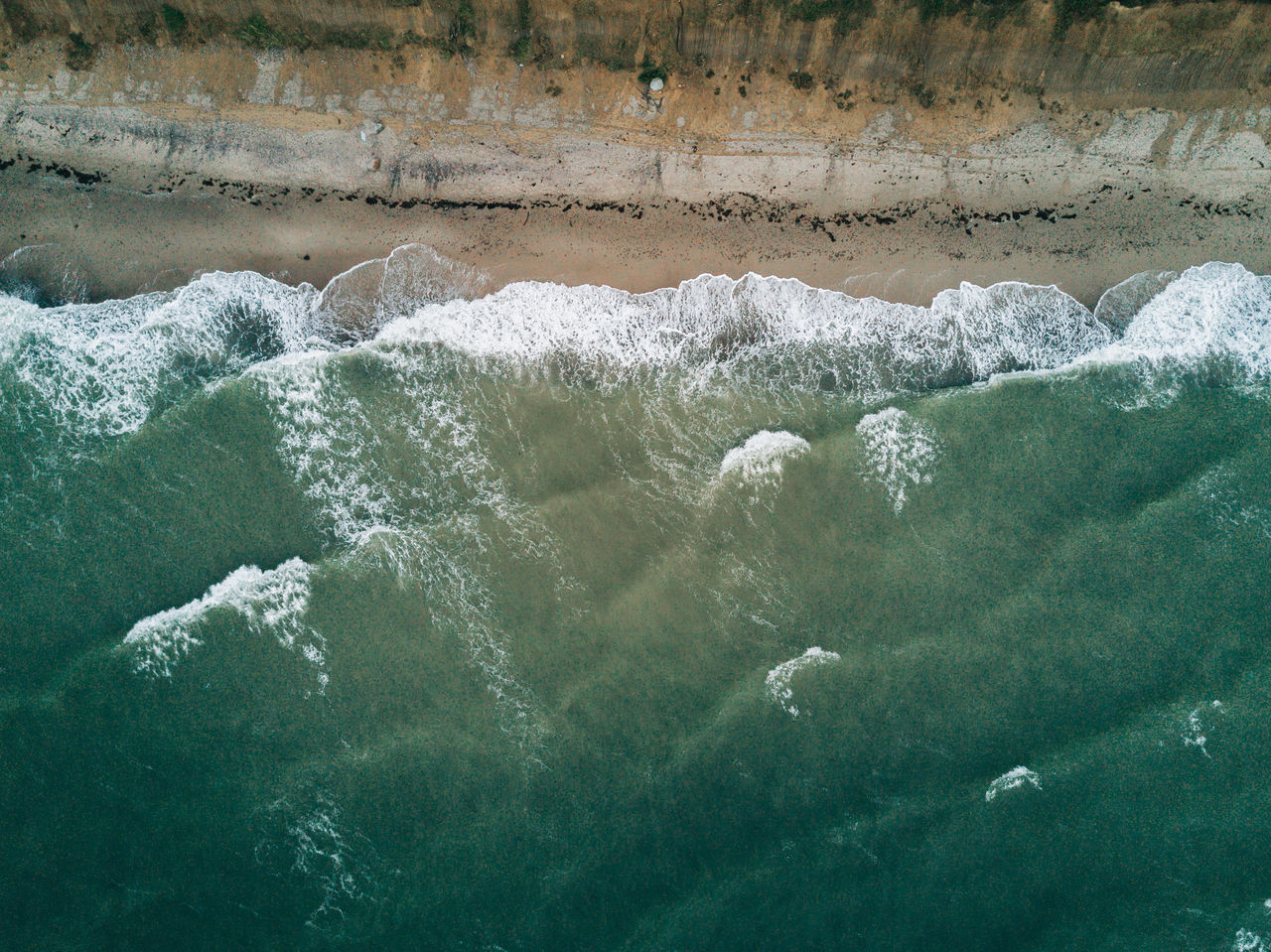 Aerial image of beach and water with waves and surfer Beauty In Nature Day Motion Nature No People Outdoors Power In Nature Water Waterfall Waterfront Wave