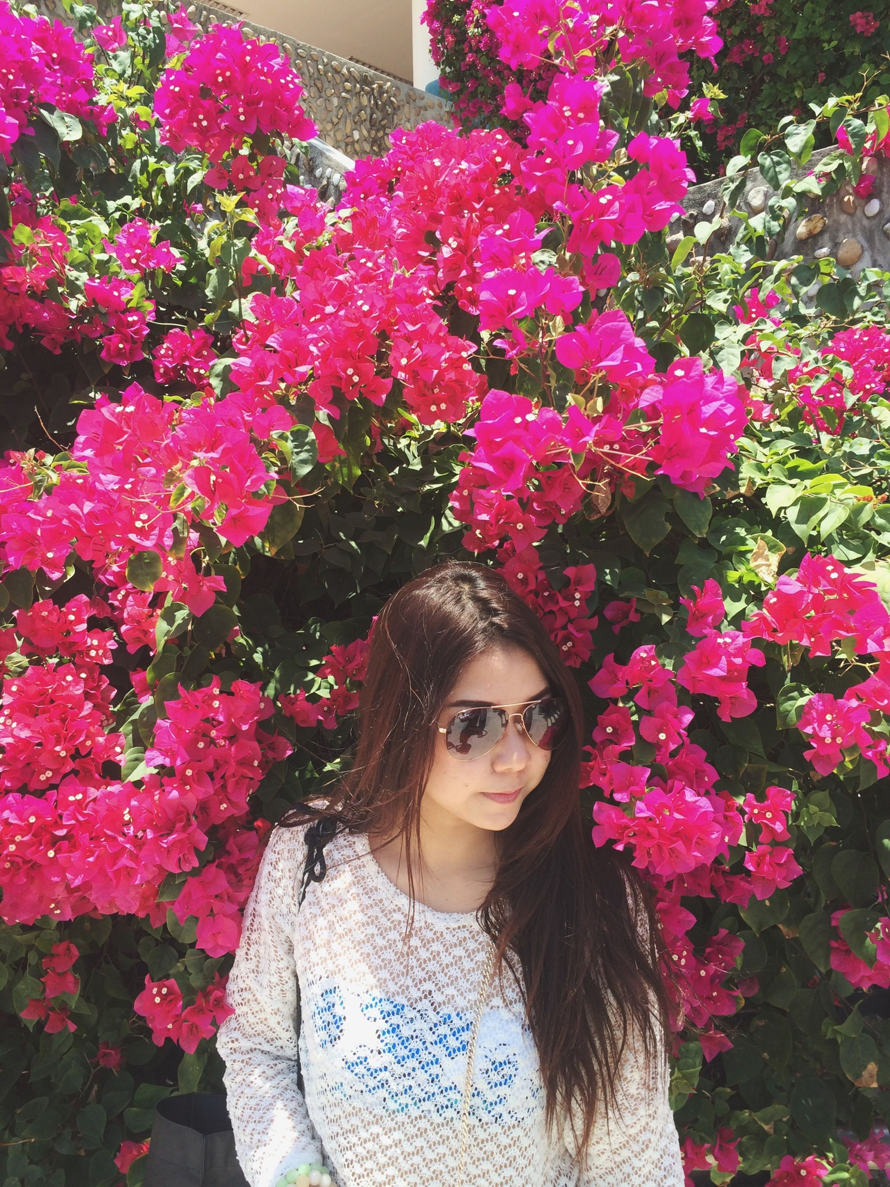 flower, young adult, person, young women, looking at camera, portrait, lifestyles, front view, pink color, smiling, long hair, leisure activity, casual clothing, tree, park - man made space, headshot, growth