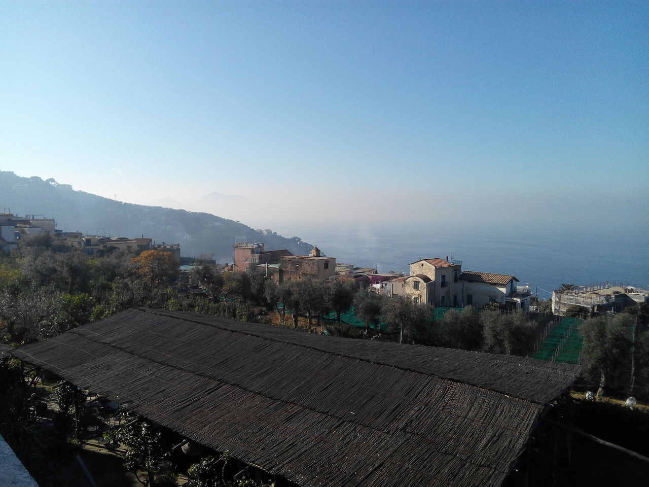 High Angle View Of Houses And Sea Against Blue Sky