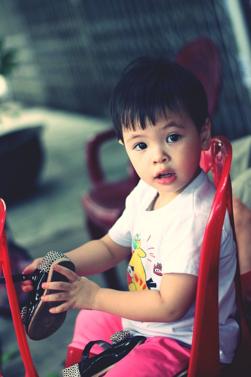 real people, sitting, childhood, one person, innocence, looking at camera, cute, portrait, focus on foreground, playing, leisure activity, outdoors, day, lifestyles, close-up, people