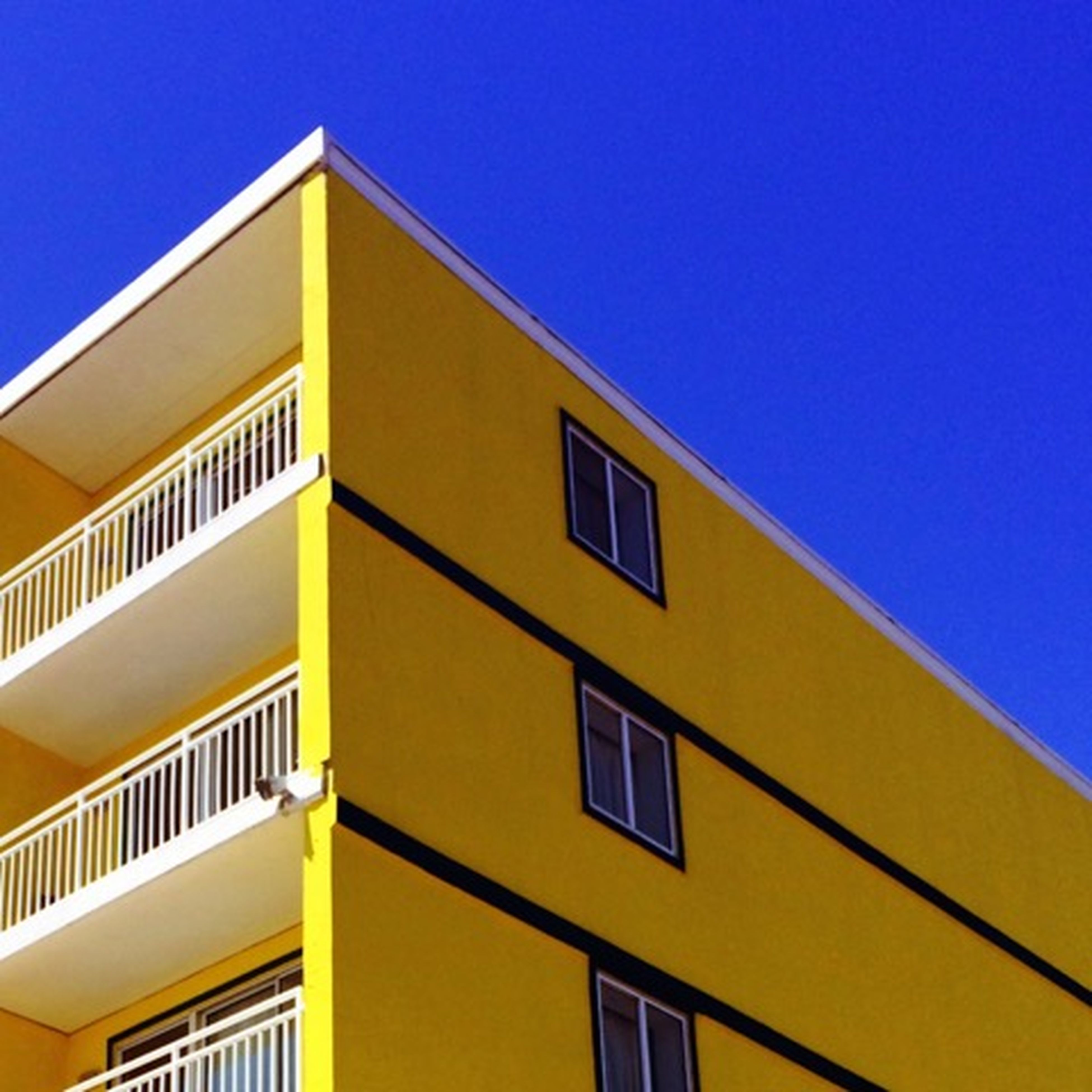 architecture, built structure, building exterior, low angle view, window, residential building, residential structure, building, clear sky, blue, yellow, house, balcony, city, no people, copy space, outdoors, day, high section, apartment