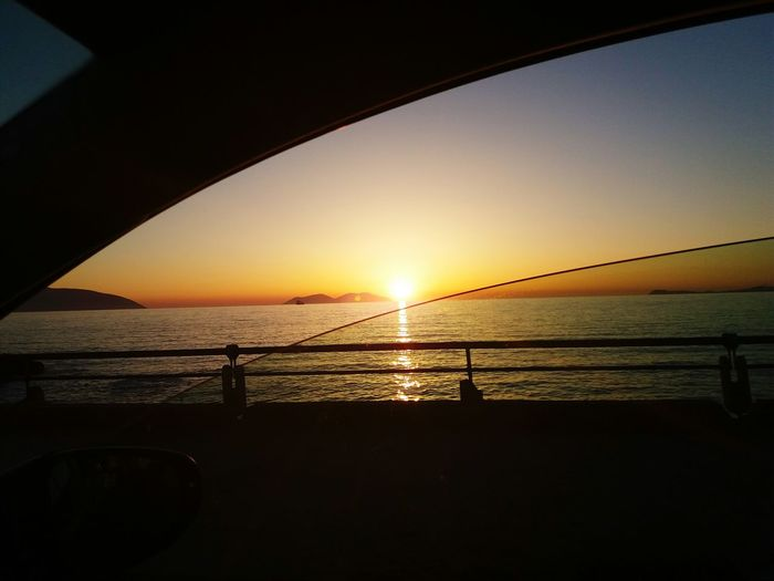 sunset on see from car window Island Vlore Albania Sea Sunset Water Silhouette Sun Sky Scenics Tranquility Horizon Over Water No People Sunlight Beach Outdoors Nature Travel Destinations Beauty In Nature City Day