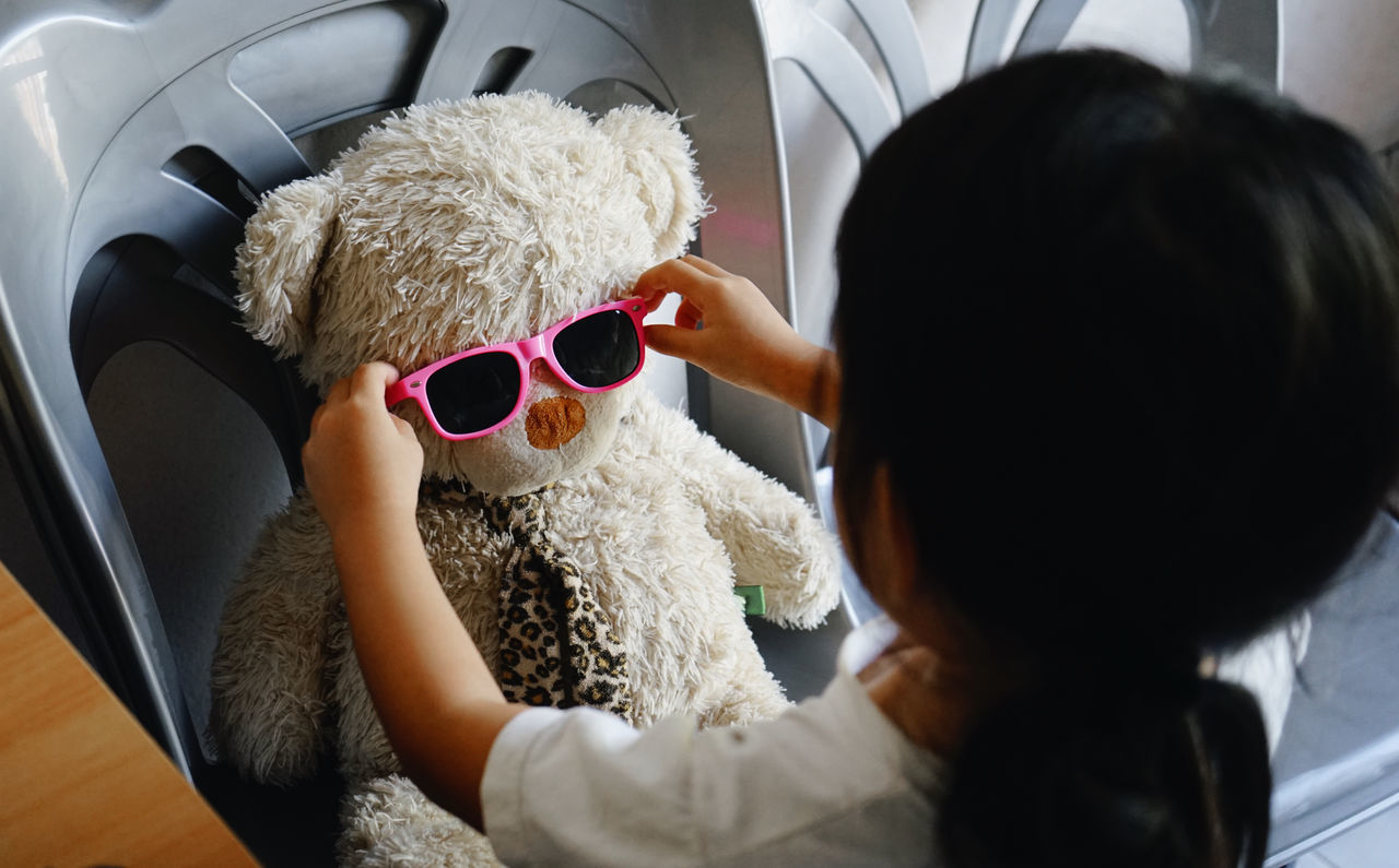 High Angle View Of Girl Wearing Sunglasses To Stuffed Toy On Chair