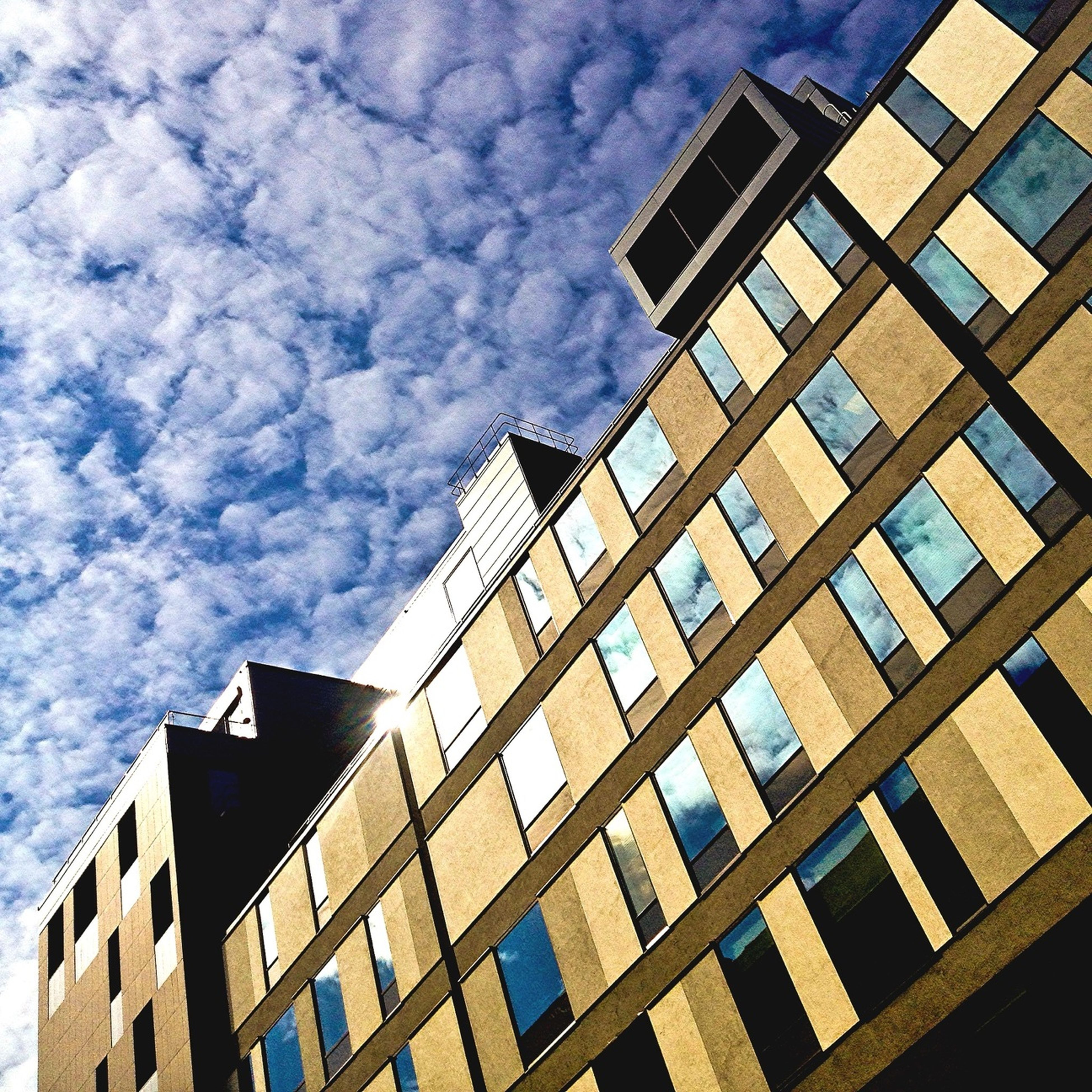 architecture, building exterior, built structure, low angle view, sky, city, window, building, modern, cloud - sky, office building, cloudy, skyscraper, glass - material, reflection, residential building, day, tall - high, cloud, outdoors