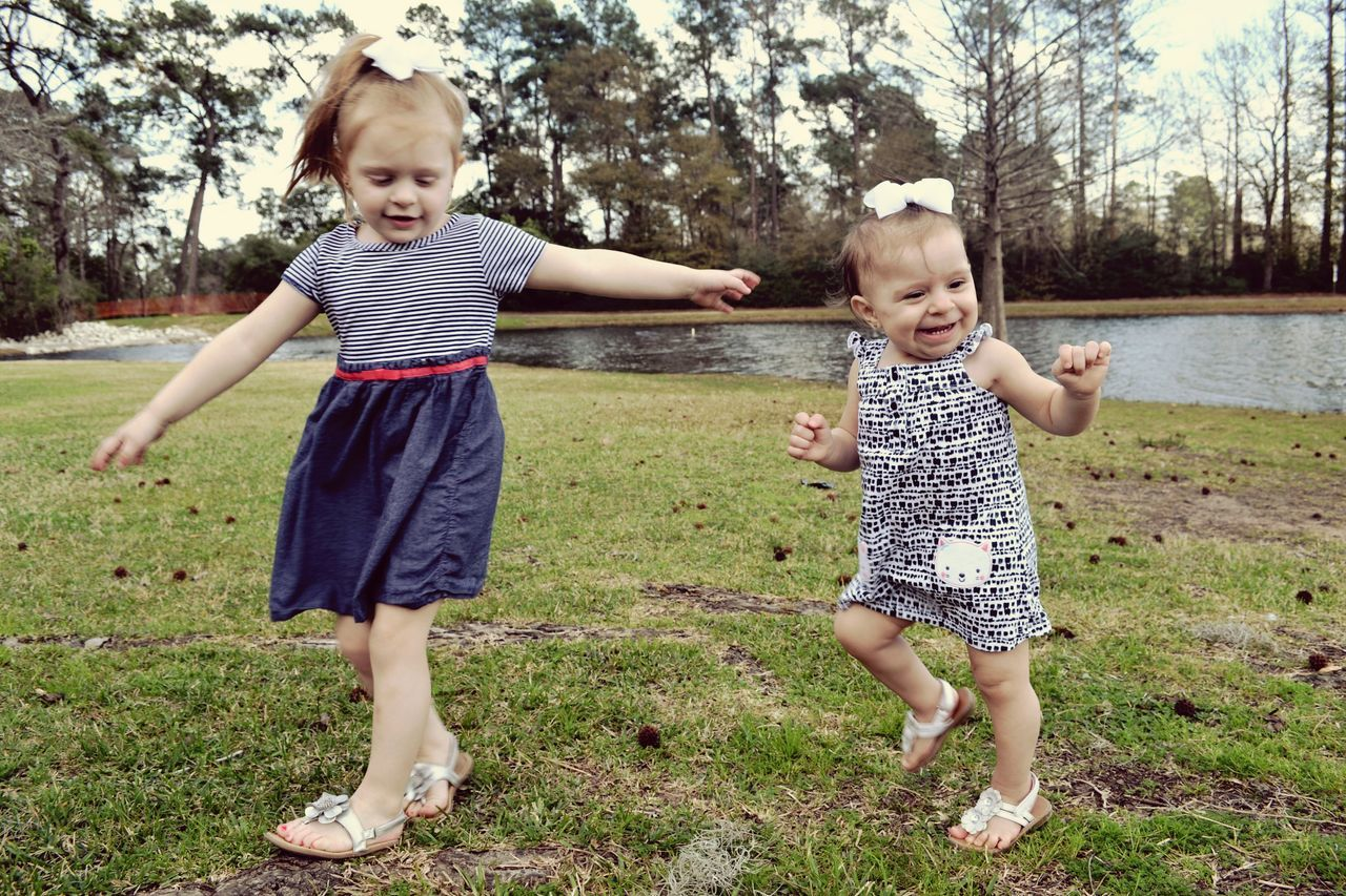 full length, childhood, tree, togetherness, happiness, looking at camera, front view, casual clothing, smiling, day, real people, two people, outdoors, grass, boys, fun, leisure activity, lifestyles, standing, bonding, portrait, girls, young adult, people