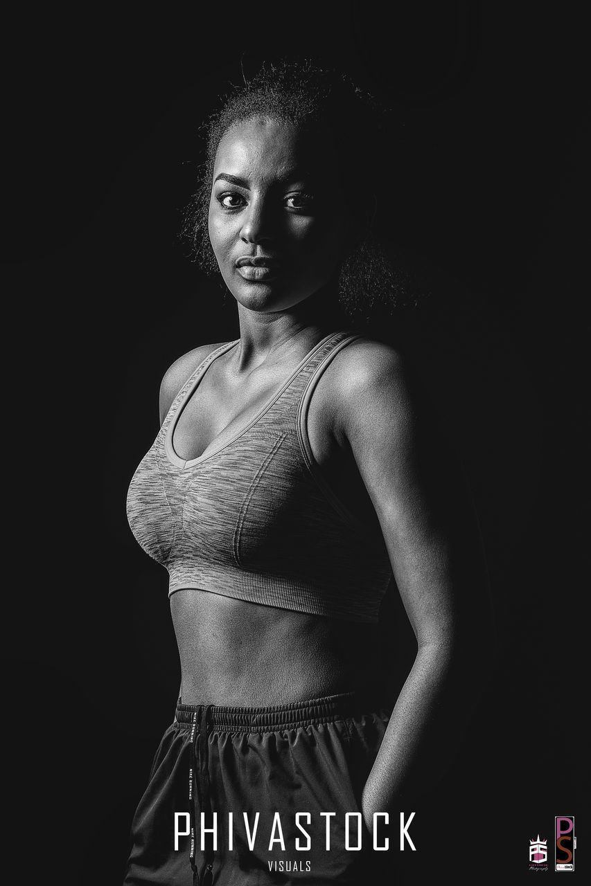 one person, waist up, real people, young adult, lifestyles, black background, looking at camera, young women, portrait, standing, studio shot, indoors, day, people