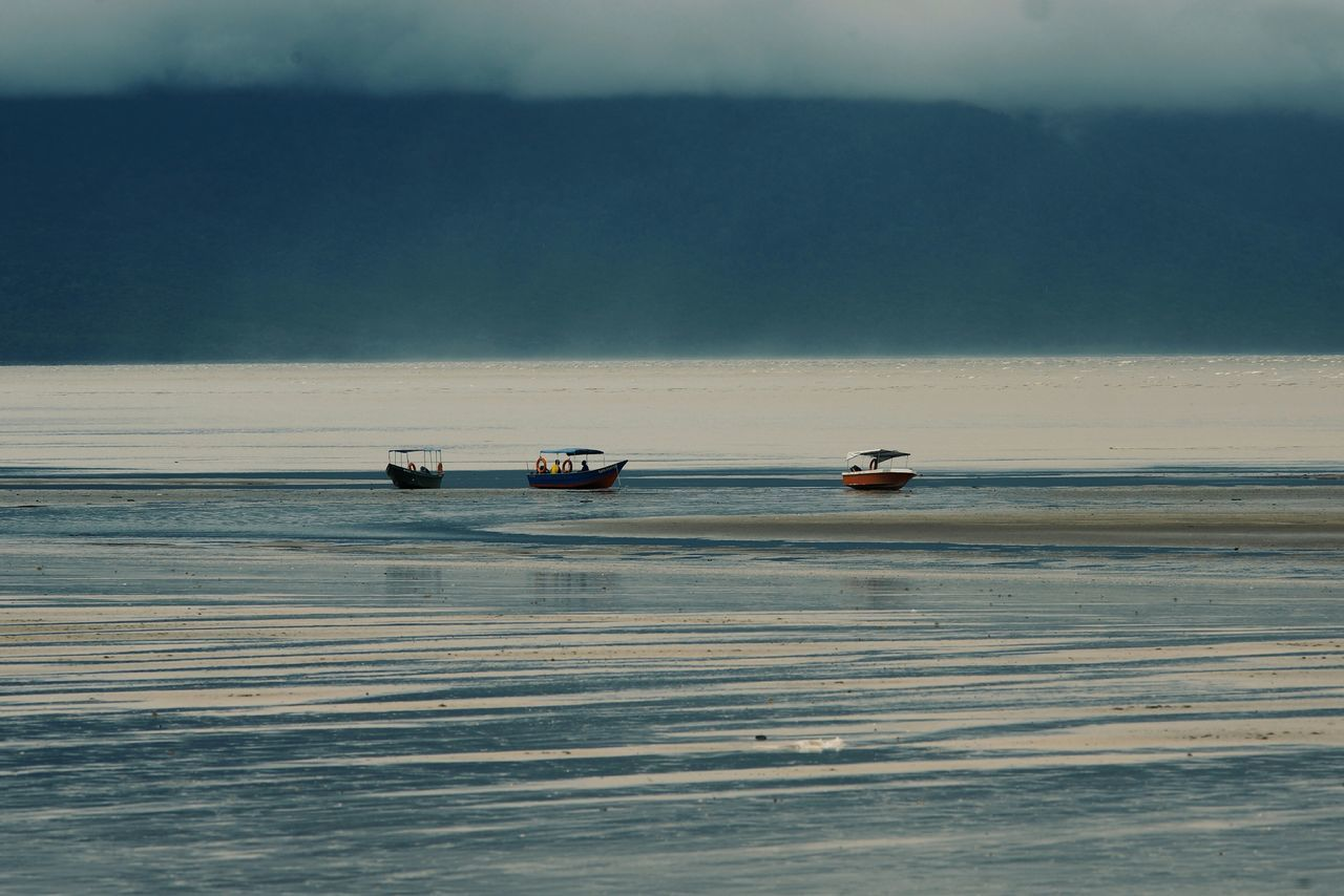 Boats Sailing In Sea Against Cloudy Sky