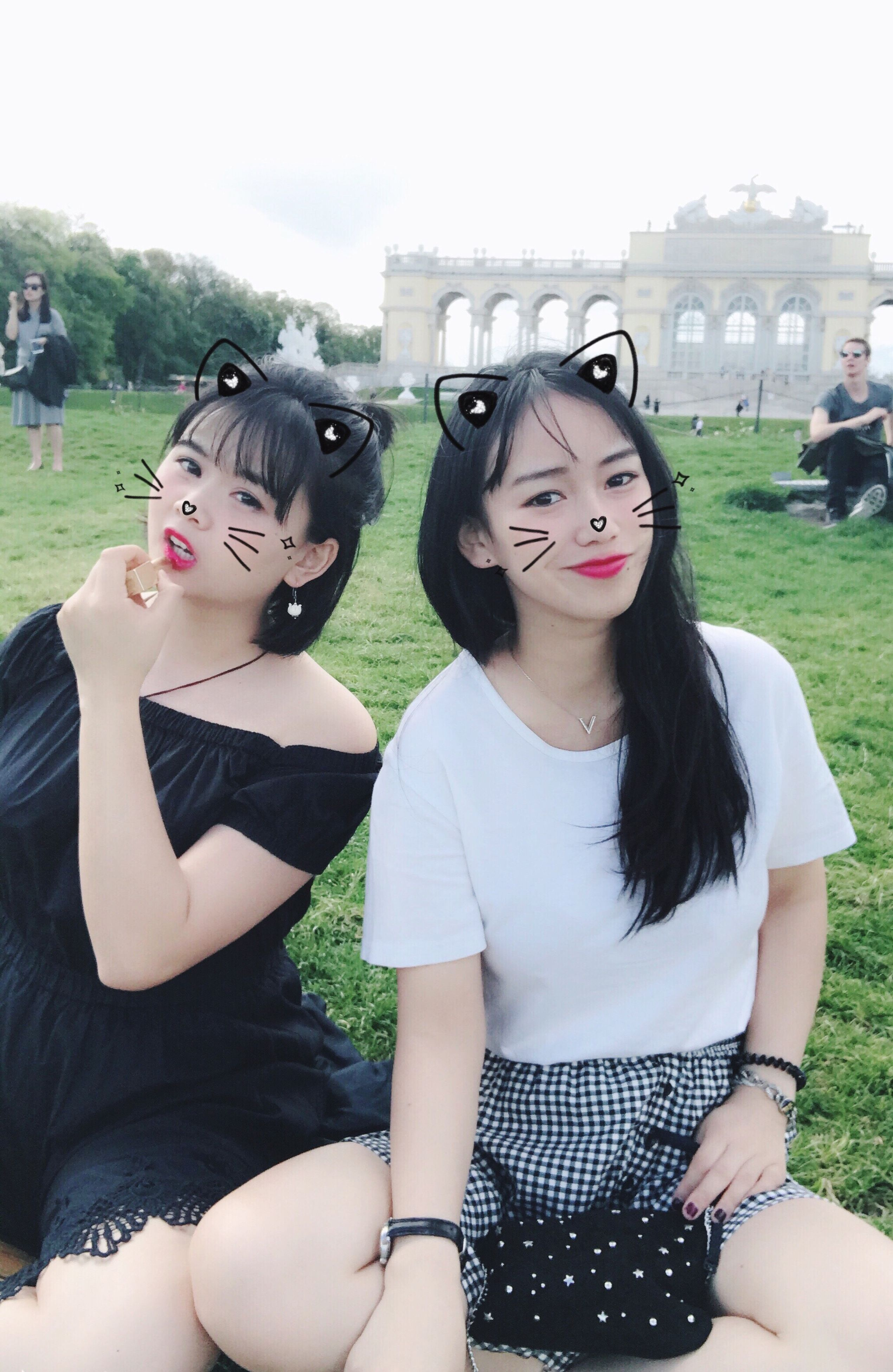 real people, black hair, young women, lawn, young adult, grass, two people, leisure activity, lifestyles, casual clothing, outdoors, day, built structure, sitting, architecture, front view, looking at camera, smiling, happiness, women, portrait, building exterior, togetherness, friendship, sky