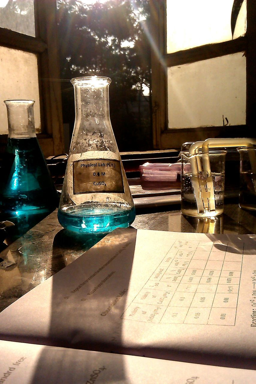 table, still life, indoors, bottle, sunlight, no people, education, laboratory, shadow, science, scientific experiment, day, close-up