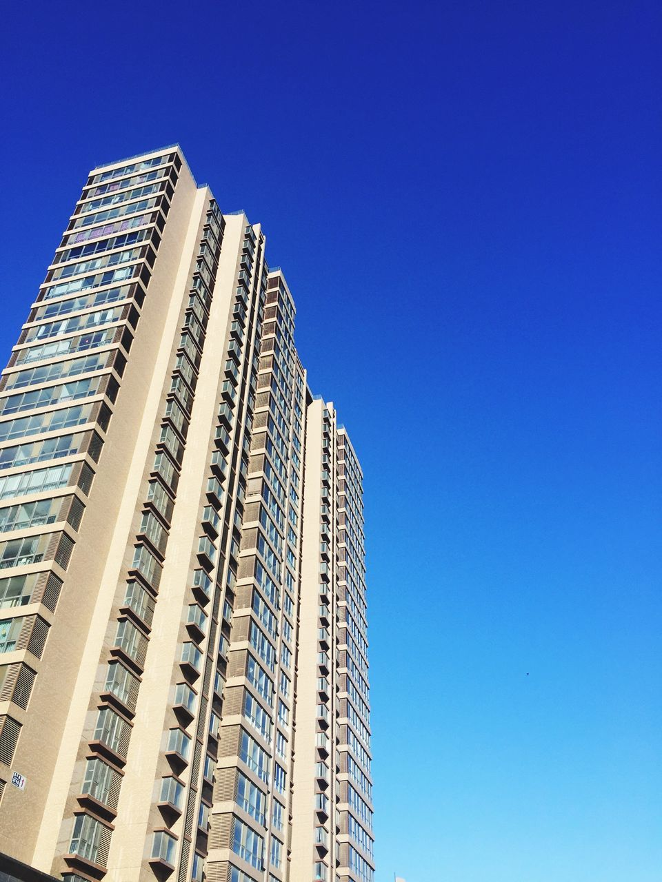 architecture, low angle view, built structure, skyscraper, building exterior, modern, blue, copy space, development, clear sky, window, city, apartment, day, no people, outdoors, cityscape, sky