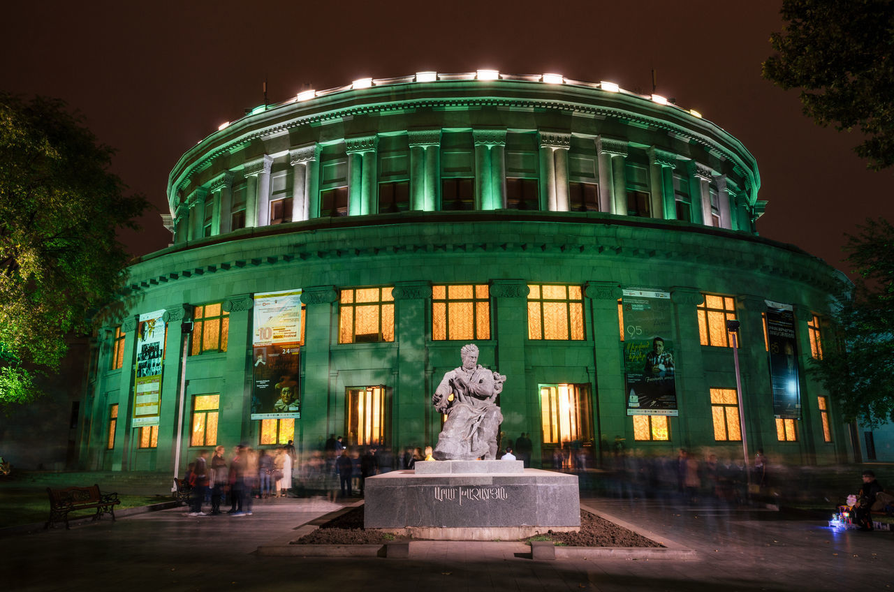 National Academic Theatre of Opera and Ballet named after Alexander Spendiaryan of Armenia illuminated at night. People come out of Armenian Opera theater. Composer Aram Khachaturian's statue. Architectural Feature Architecture Architecture Arena Green Illuminated Night OpenEdit Outdoors People People Walking  Sculpture Statue Yerevan