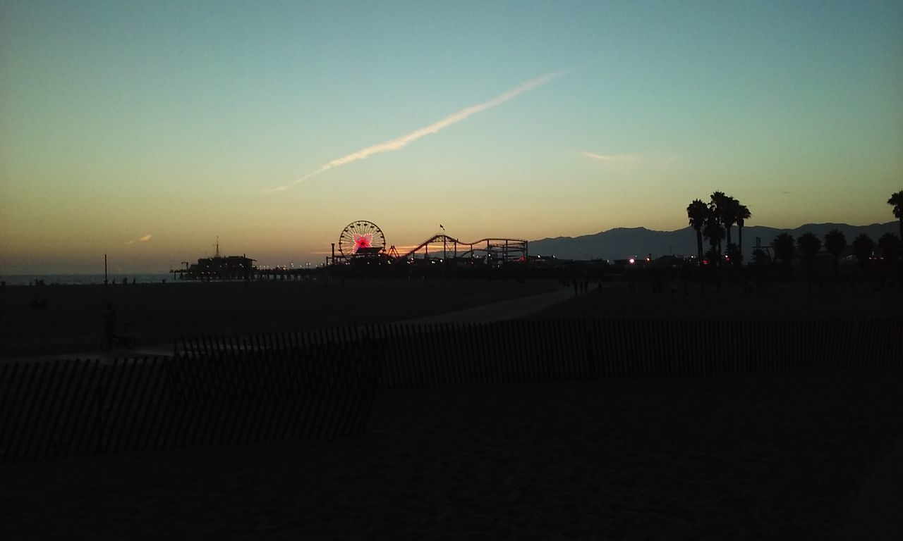 sunset, built structure, sky, architecture, outdoors, nature, beach, silhouette, building exterior, water, beauty in nature, ferris wheel, no people, day