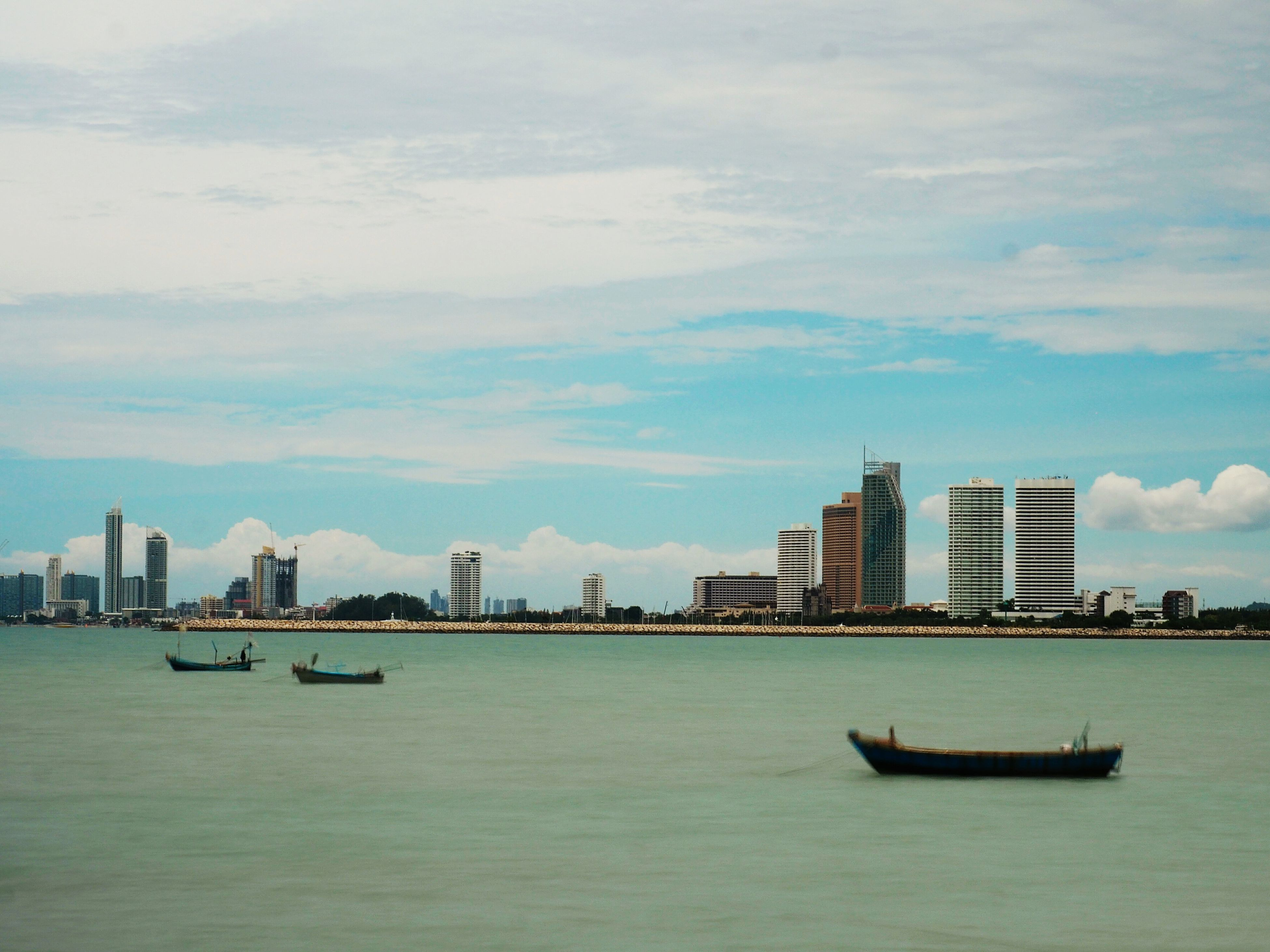 waterfront, architecture, water, built structure, nautical vessel, sky, city, boat, river, cloud - sky, cityscape, urban skyline, cloud, mid distance, day, rippled, outdoors, ship, no people, nature, tall - high, cloudy, travel destinations, tranquility, blue, development