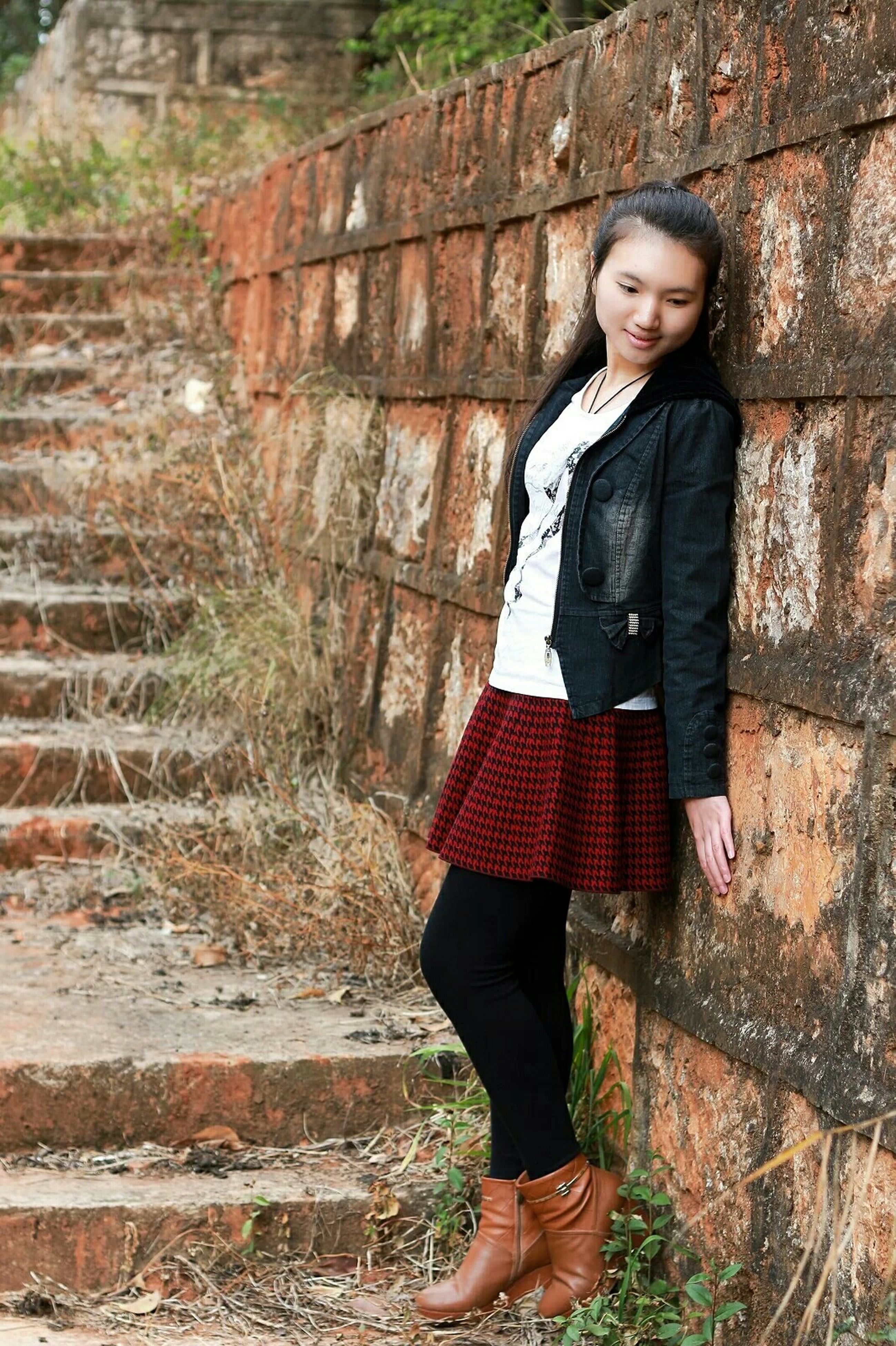 casual clothing, young adult, standing, architecture, built structure, building exterior, lifestyles, person, front view, young women, portrait, looking at camera, brick wall, full length, wall - building feature, hands in pockets, three quarter length, leisure activity