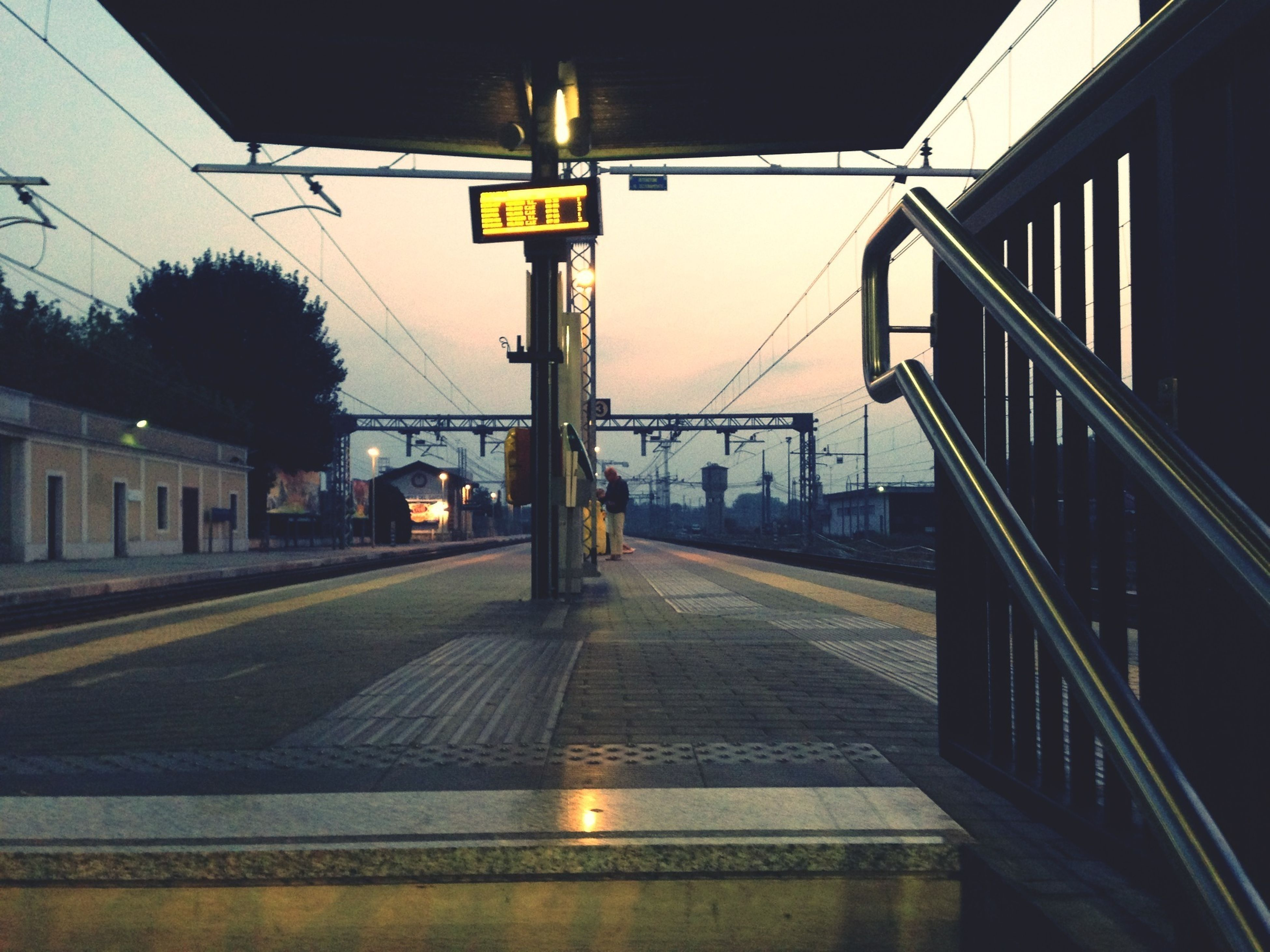 built structure, architecture, transportation, railroad station, rail transportation, public transportation, railroad track, building exterior, railroad station platform, illuminated, city, connection, text, communication, train - vehicle, information sign, the way forward, city life, clear sky, sky
