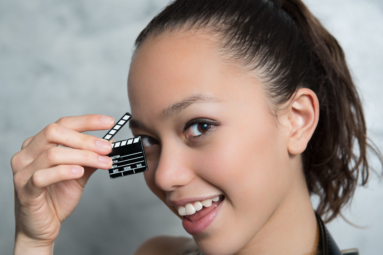 Young pretty woman with little movie clapper board headshot Asian Ethnicity Beautiful Beautiful Woman Clapboard Clapper Clapper Board Clapperboard Close-up Day Gray Background Headshot Holding Indoors  Looking At Camera MOVIE Movies One Person People Pretty Girl Studio Shot Young Women