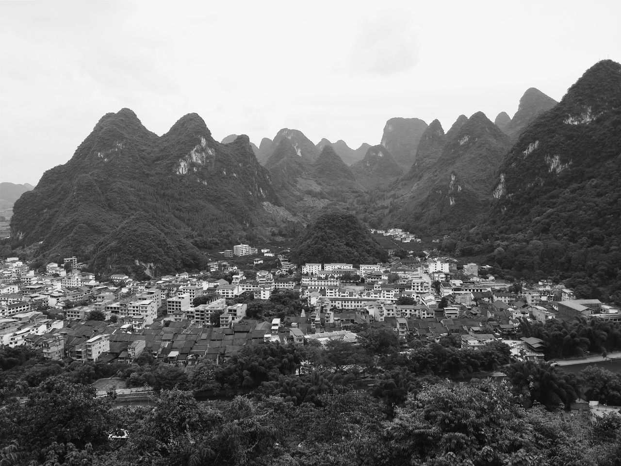 High Angle View Of Town By Mountain Range Against Sky