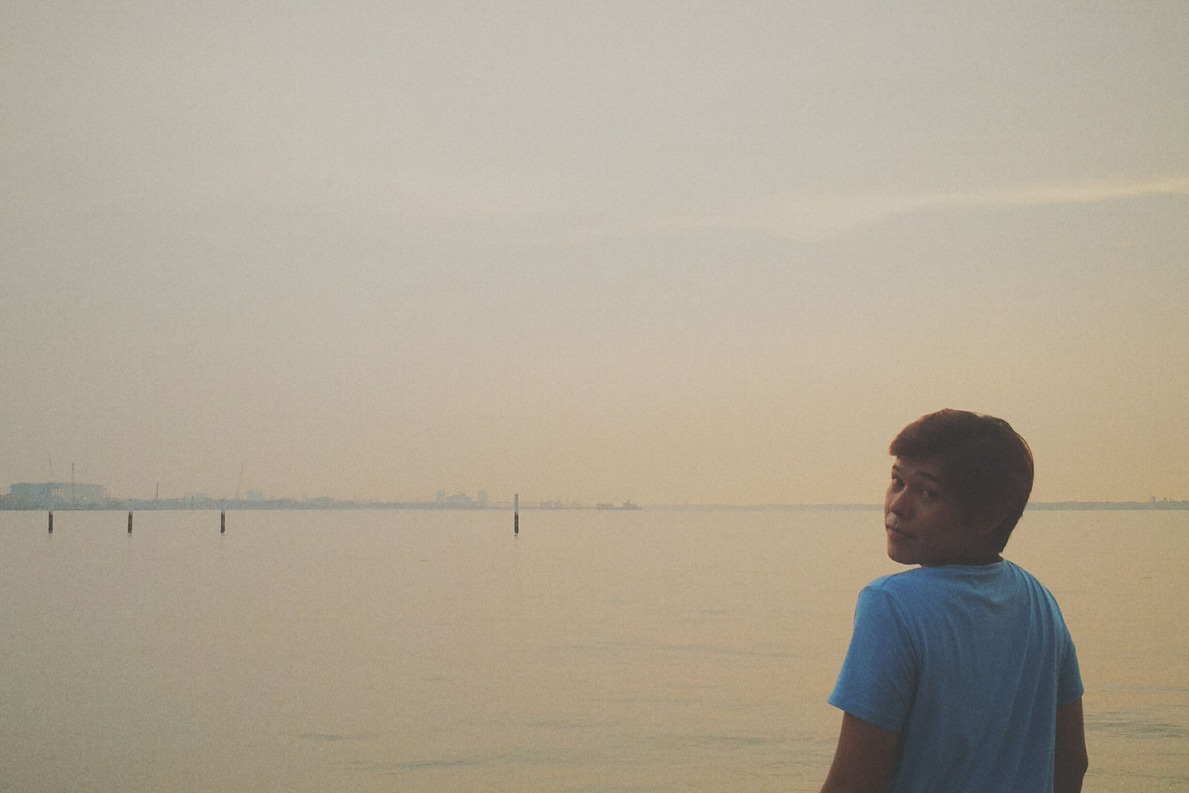 lifestyles, sea, copy space, water, leisure activity, beach, clear sky, rear view, standing, tranquility, tranquil scene, nature, casual clothing, men, scenics, horizon over water, shore, beauty in nature