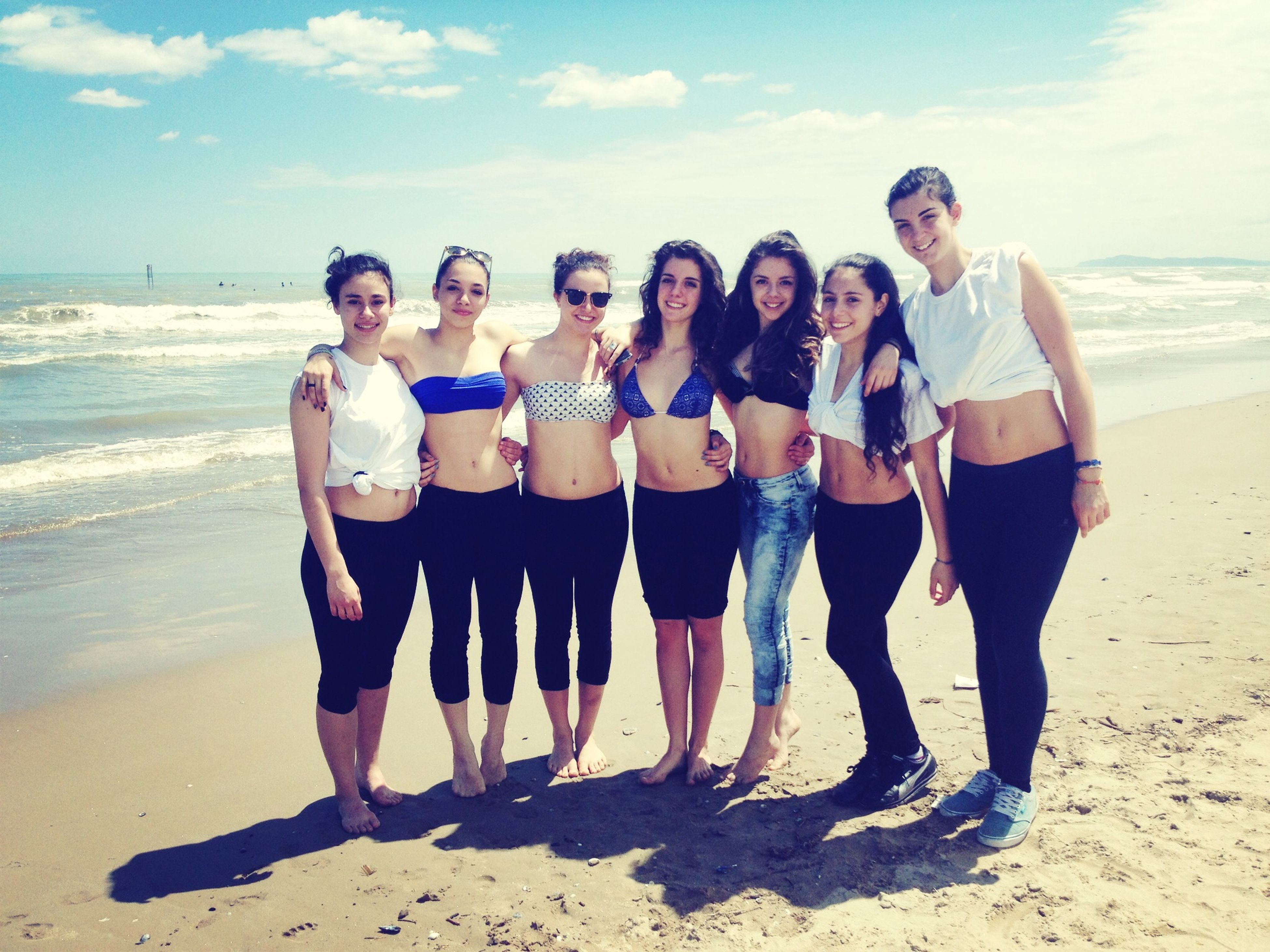 beach, sea, lifestyles, water, togetherness, leisure activity, sand, shore, sky, full length, casual clothing, vacations, bonding, standing, horizon over water, love, friendship, person