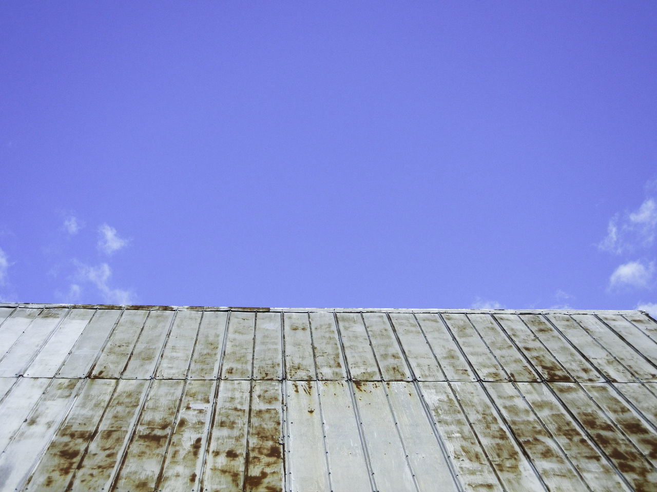 Worn urban roof scape under a bright blue sky. Architecture Blue Bright Building Built Structure City Cityscape Clear Sky Day Low Angle View No People Outdoors Roof Roofline Rust Urban