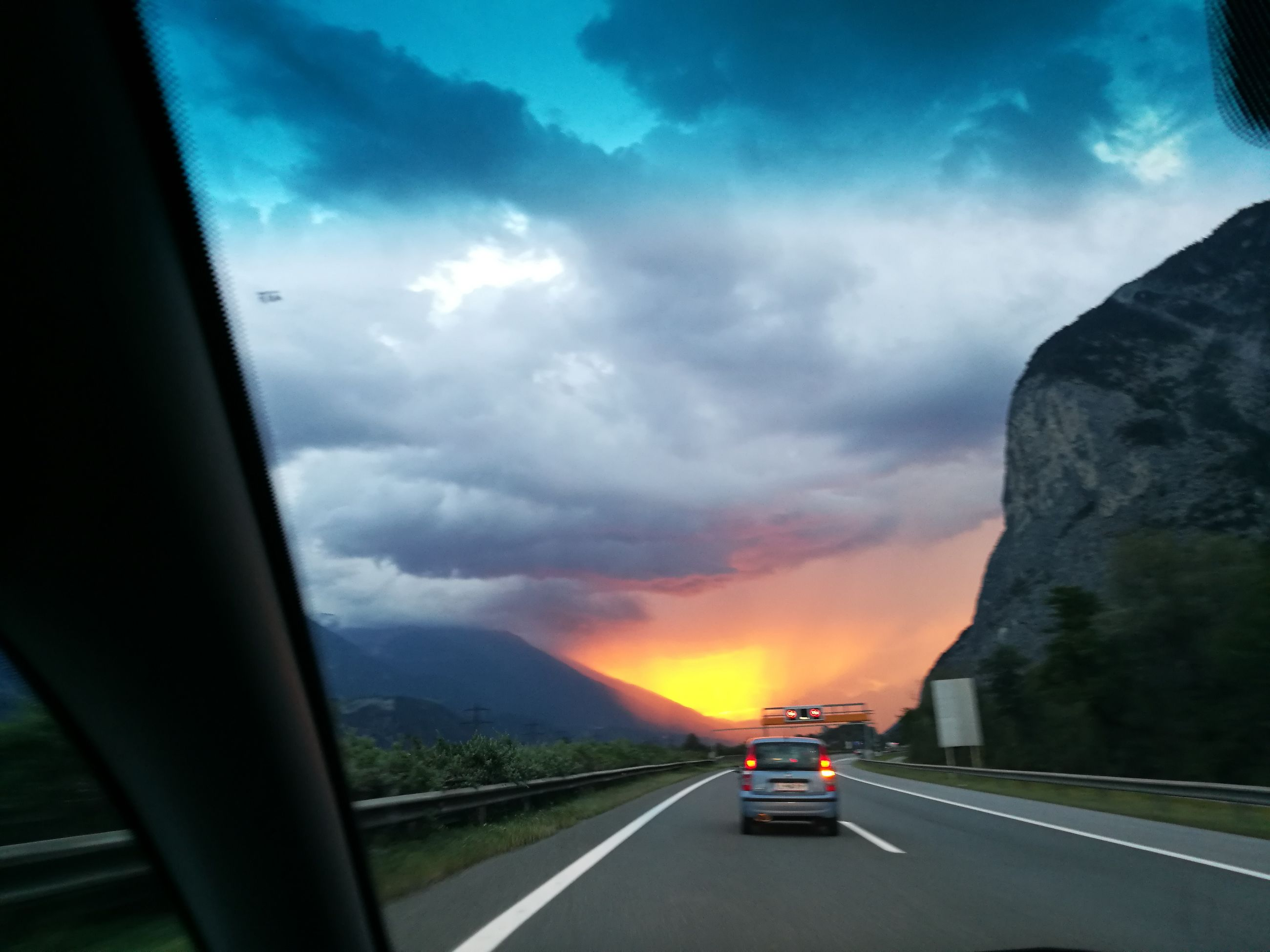 transportation, road, car, mode of transport, land vehicle, on the move, the way forward, road marking, journey, cloud - sky, travel, cloud, sky, orange color, road trip, blue, tail light, mountain, dramatic sky, vehicle, country road, vanishing point, dividing line, diminishing perspective, scenics, long, cloudy