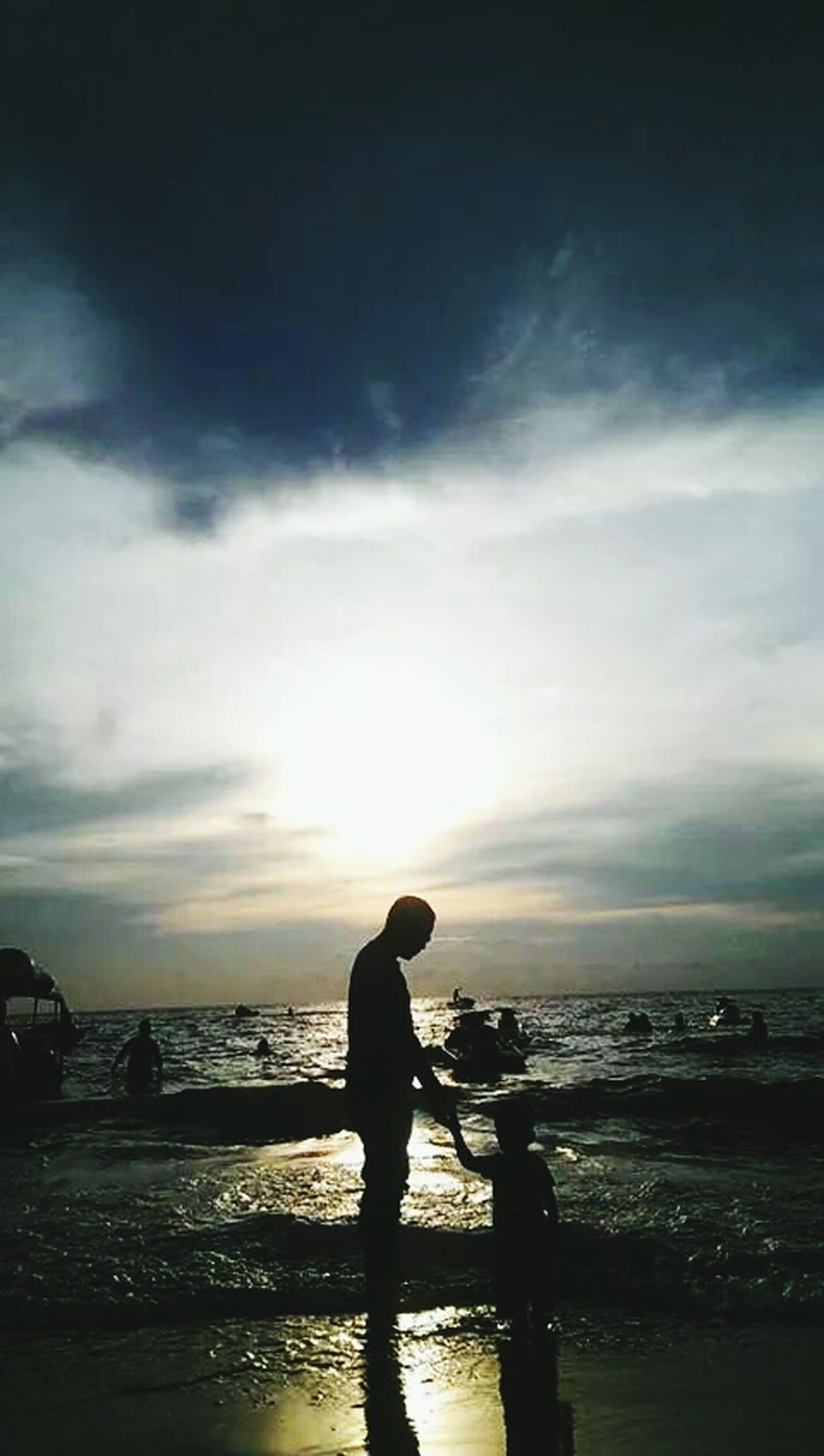 sea, silhouette, water, sunset, horizon over water, sky, beach, scenics, tranquil scene, standing, beauty in nature, shore, tranquility, lifestyles, leisure activity, cloud - sky, sun, nature