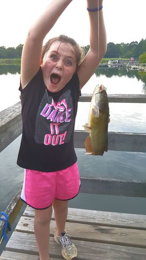Showing Expression Girl Fishing Fishing Emotions Lake Water One Girl Only Child Mouth Open Childhood Funny Faces Happy Catching Fish Holding Fish Excitement Proud Moment  Nature Lover Catfish Dock Dock On Water Fishing Dock Aquatic Wildlife Catch And Release Outdoor Activity Pet Portraits