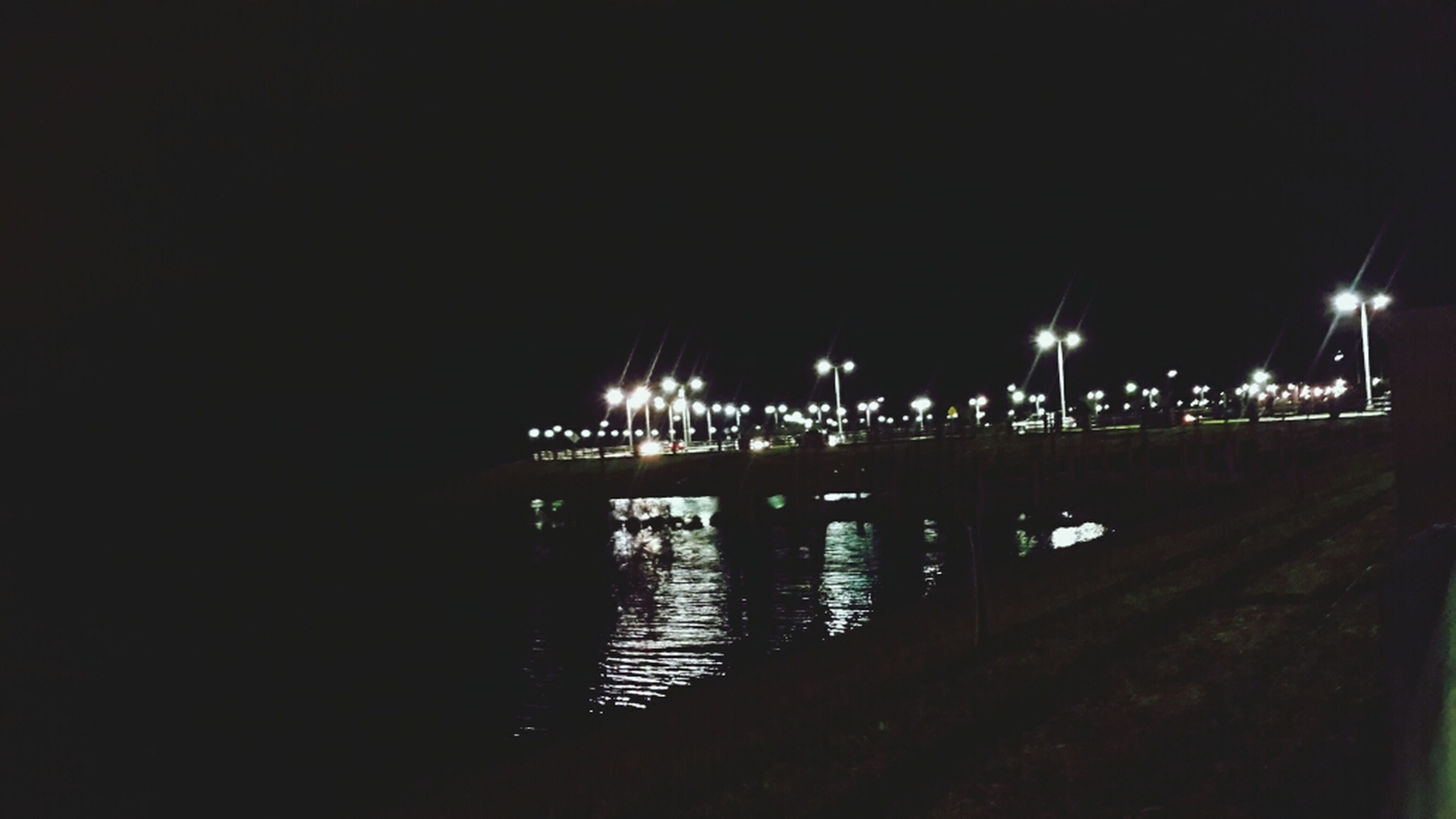 night, illuminated, water, reflection, built structure, architecture, dark, river, waterfront, street light, lighting equipment, copy space, clear sky, building exterior, city, outdoors, no people, bridge - man made structure, connection, transportation