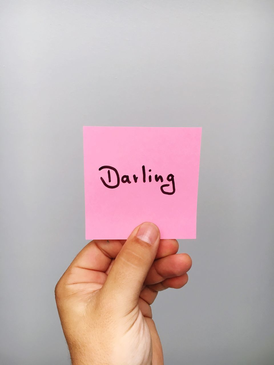 Cropped Hand Of Person Holding Adhesive Note With Darling Text Against Gray Background