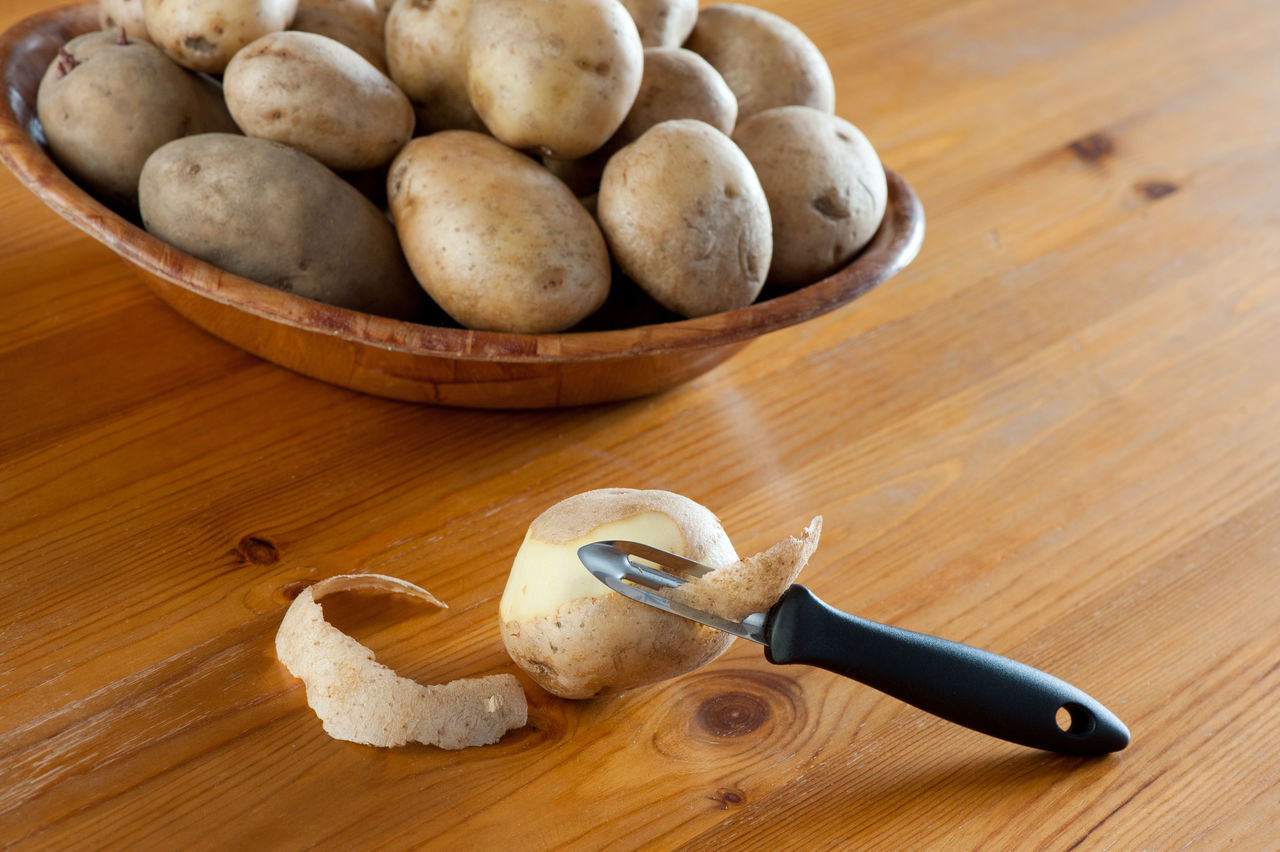 Potato peeler and peelings of tuber, many vegetables lying on bamboo bowl on wooden table, horizontal orientation, nobody, daylight from window. Accessory Domestic Equipment Food Food And Drink Heap Kitchen Utensils No People Peel Peeler Peeling Peeling Off Pile Potato Potatoes Roots Scraping 🍄 Solanum Spud  Spuds Table Tubers Vegetable Vegetables