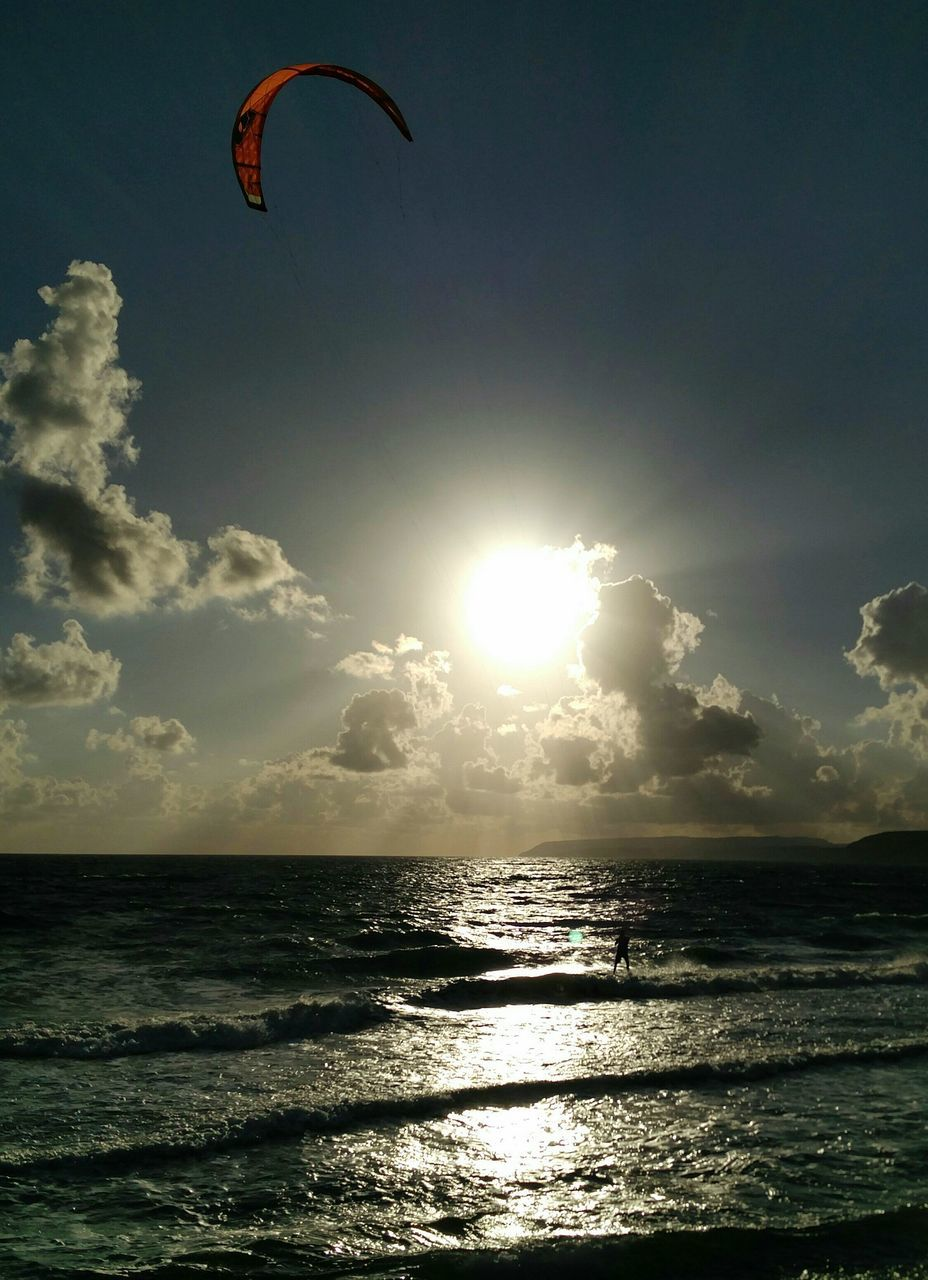 sea, sunlight, sun, sunbeam, nature, scenics, horizon over water, sky, sunset, beauty in nature, water, outdoors, leisure activity, adventure, tranquil scene, sport, extreme sports, parachute, silhouette, tranquility, vacations, beach, real people, cloud - sky, one person, day, paragliding, people