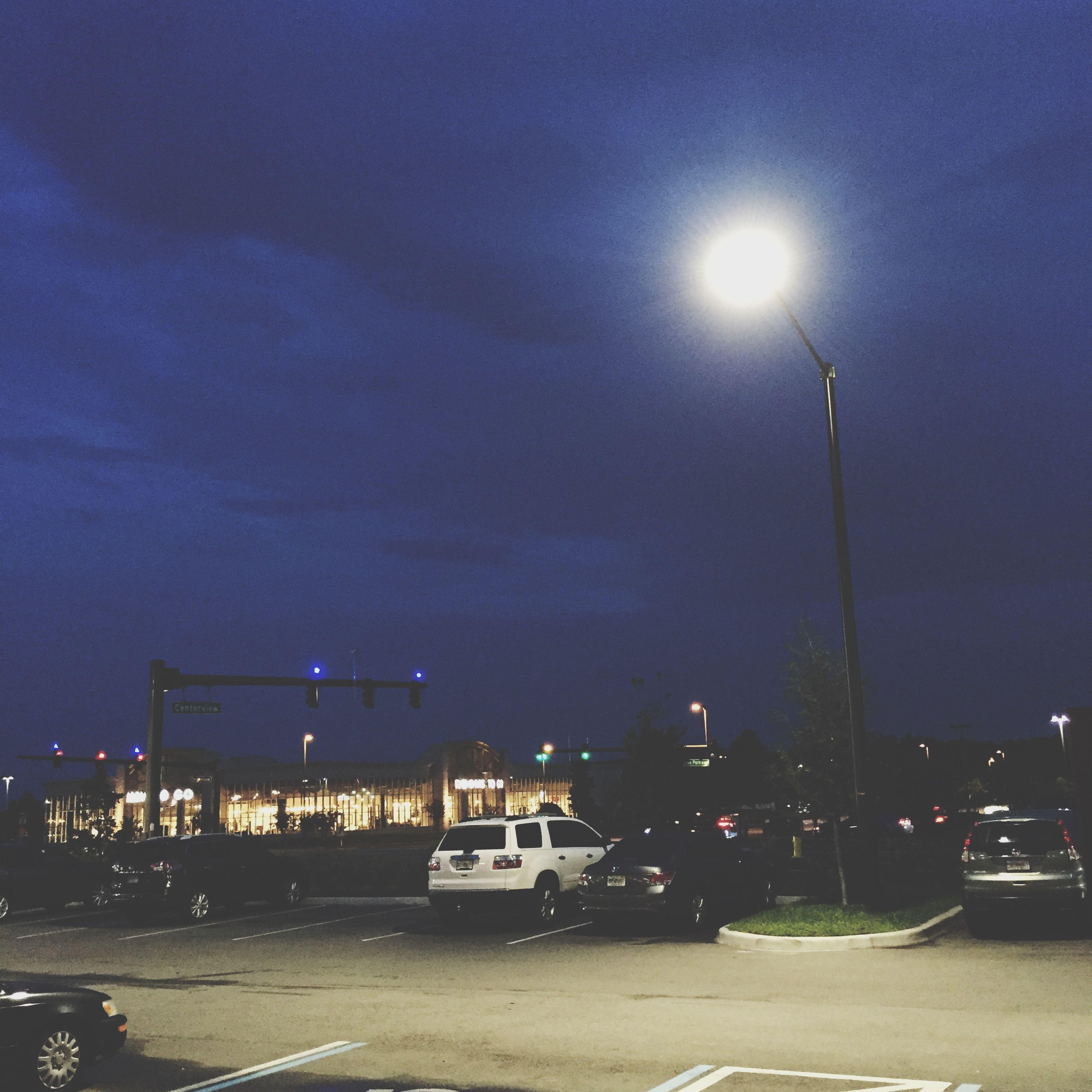 street light, illuminated, night, sky, transportation, car, street, land vehicle, building exterior, lighting equipment, road, mode of transport, built structure, architecture, cloud - sky, city, dusk, weather, outdoors, city street