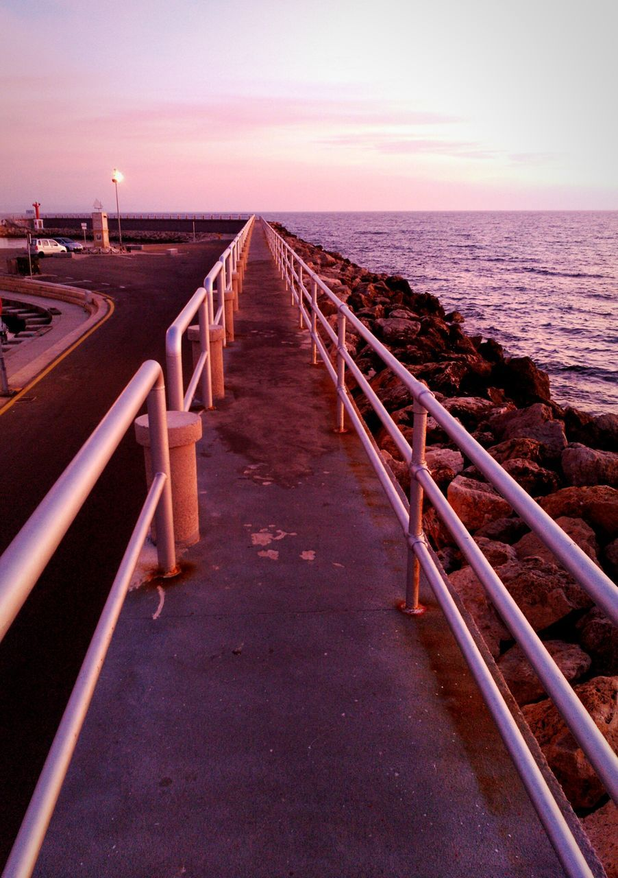 sea, horizon over water, water, railing, sunset, scenics, tranquil scene, nature, sky, beauty in nature, tranquility, outdoors, beach, no people, clear sky, day
