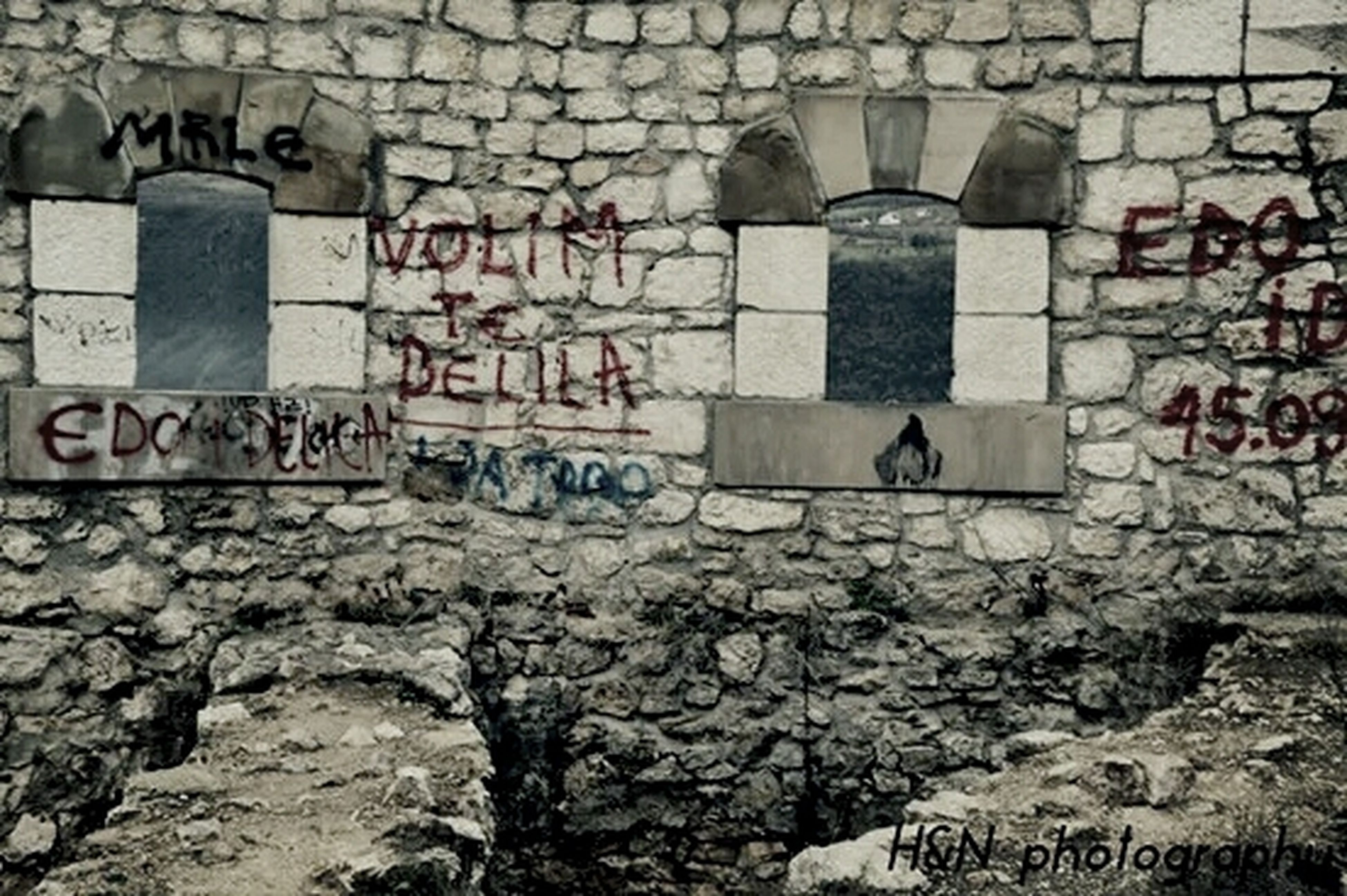 architecture, built structure, wall - building feature, building exterior, text, brick wall, graffiti, stone wall, old, western script, communication, wall, history, weathered, abandoned, damaged, day, obsolete, outdoors, deterioration