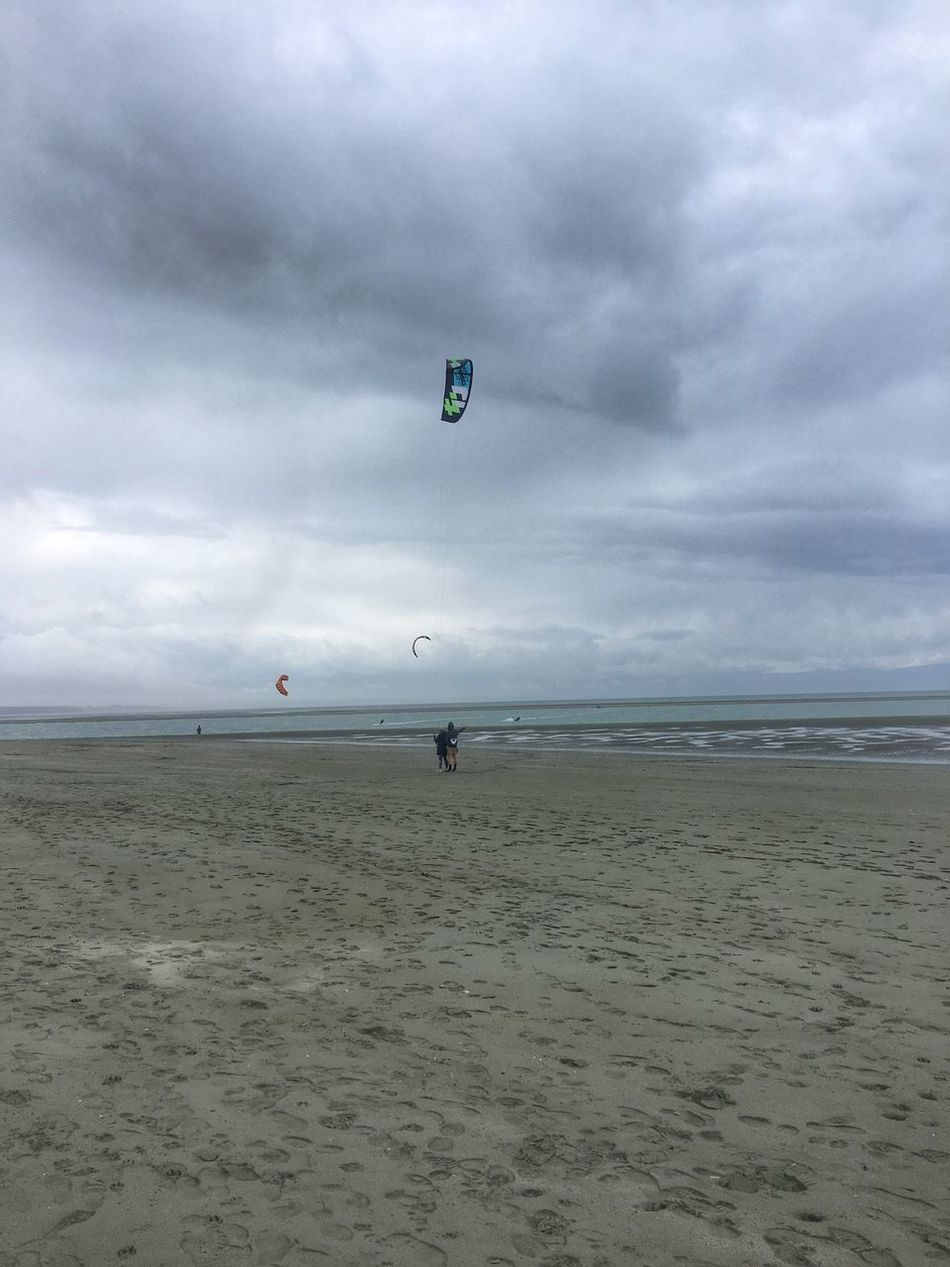 Some kite surfing happening Beach Sand Lifestyles Leisure Activity Cloudy Kite Surfing Surfing People People Watching People At The Beach