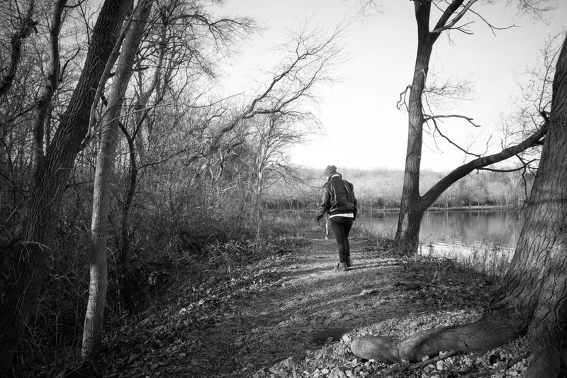 Bare Trees Beauty In Nature Black And White By The Water Casual Clothing Cold Day Full Length Growth Hiking Lake Leisure Activity Lifestyles Nature Nature Path No Recognizable People Outdoors Portrait Season  Tranquil Scene Tranquility Tree
