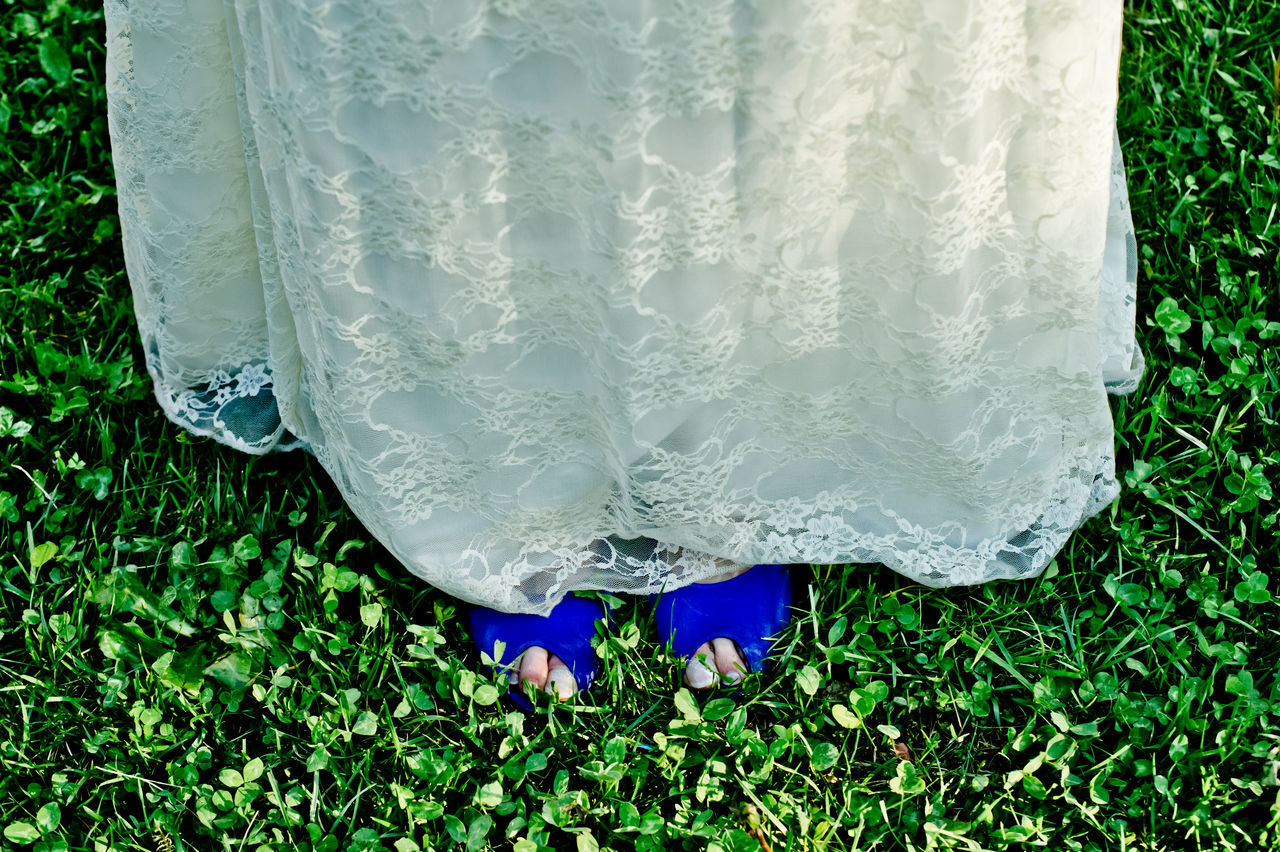 Low Section Of Bride Standing On Green Field