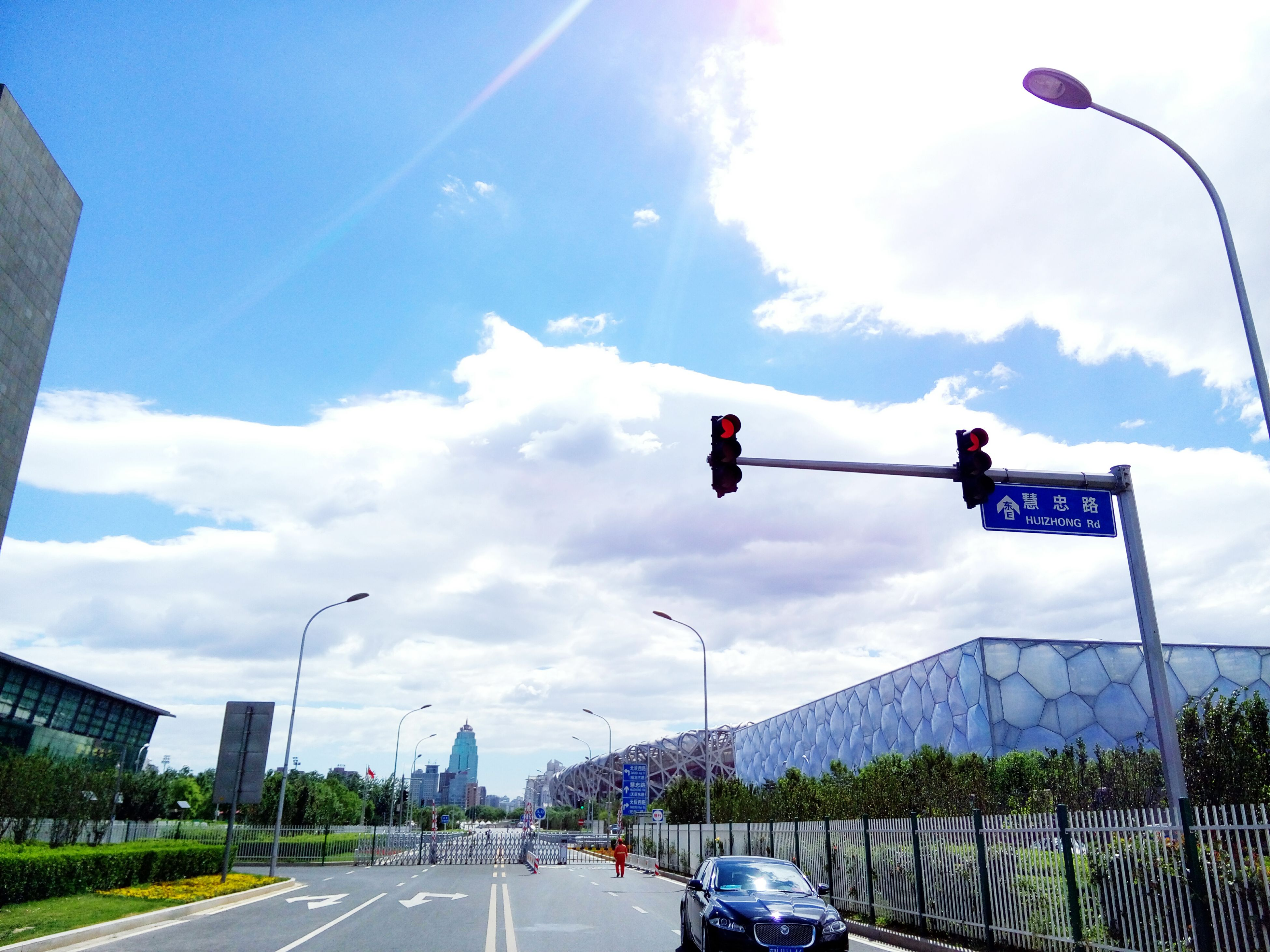 transportation, road, land vehicle, car, sky, the way forward, road marking, mode of transport, street, street light, built structure, cloud - sky, architecture, building exterior, diminishing perspective, city, cloud, road sign, on the move, vanishing point