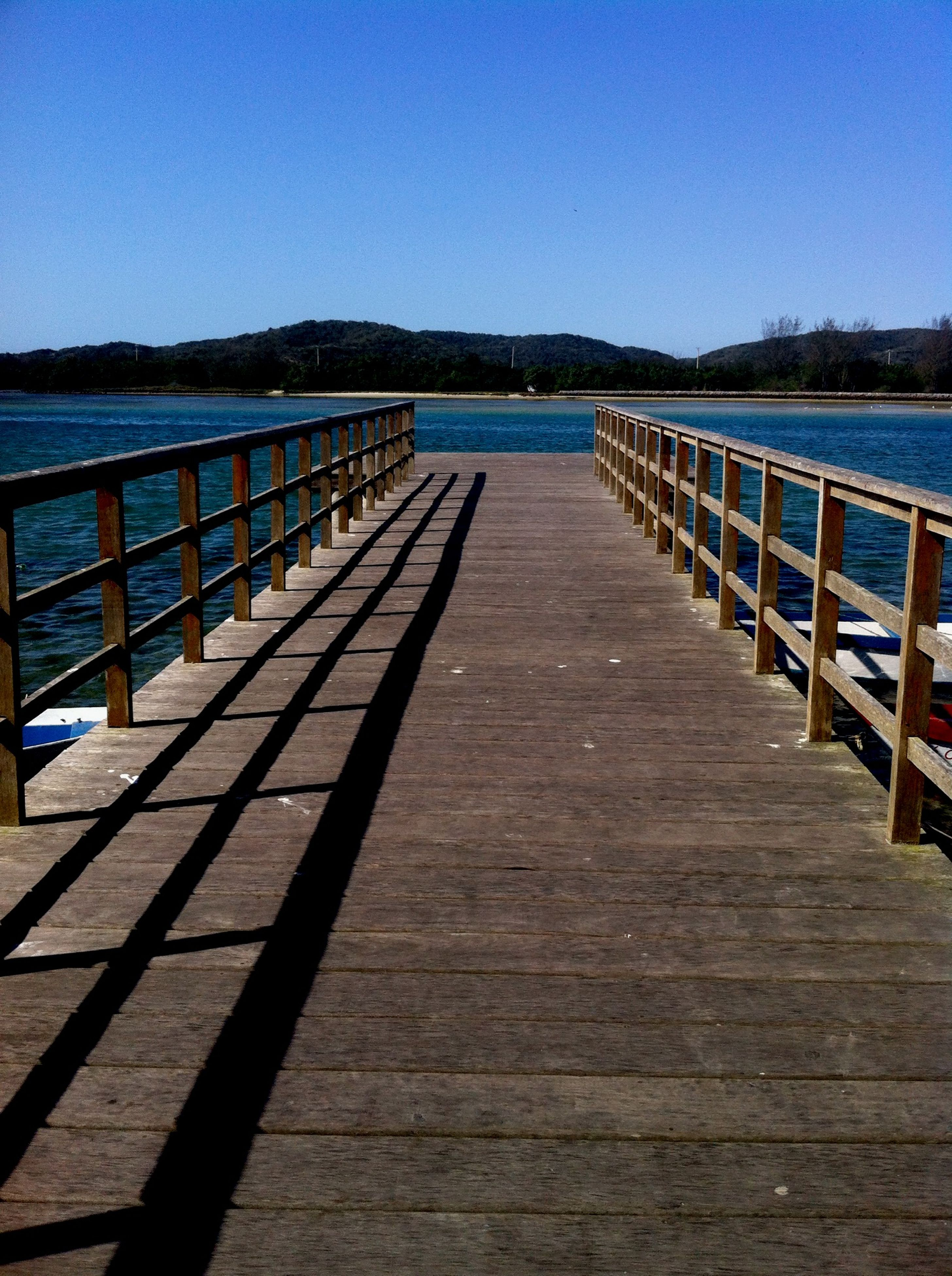 water, the way forward, blue, clear sky, pier, railing, tranquility, tranquil scene, diminishing perspective, boardwalk, wood - material, sea, copy space, scenics, jetty, long, nature, beauty in nature, vanishing point, wood