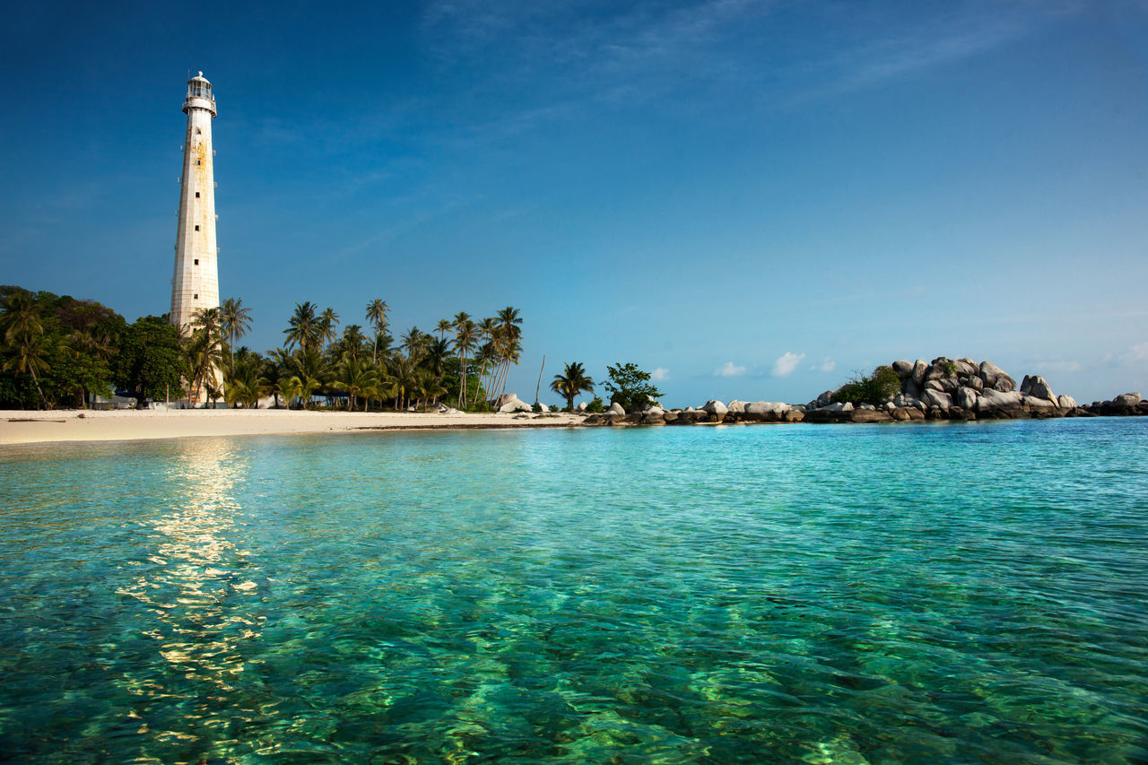 White lighthouse standing on an island in Belitung at daytime surrounded by clear blue green turquoise colored ocean water. Beach Belitung Belitung Island Blue Ocean Blue Sky Blue Sea And Clear Water Blue Skies Clear Ocean Clear Water Beach Coast Coastline Landscape Green Ocean Green Sea Island Lighthouse Lighthousephotography Ocean Reflections In The Water Rocks And Water Seashore Seashore Photography Tropical Climate Tropical Paradise Turquoise Water White Lighthouse White Sand Beach EyeEmNewHere