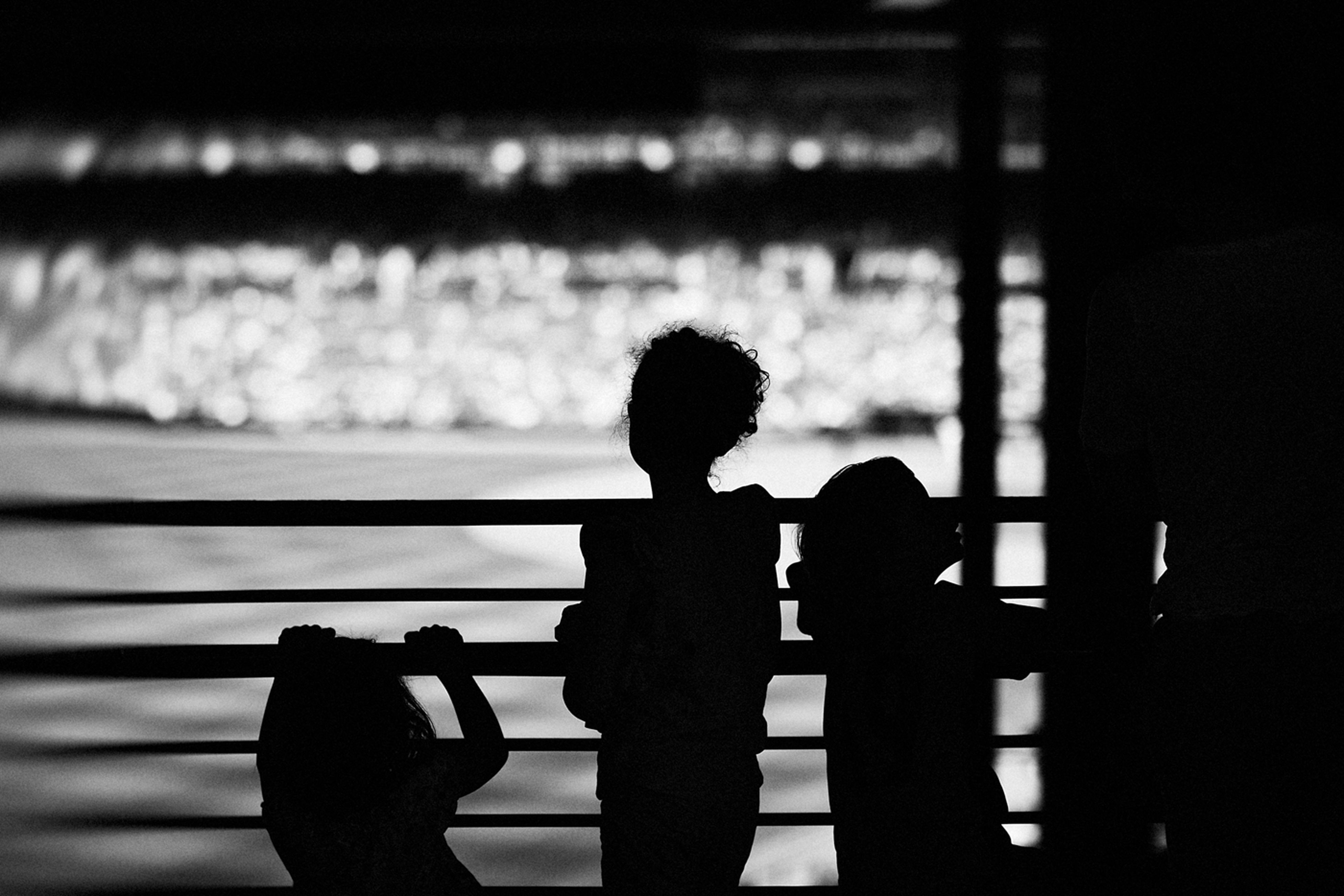 silhouette, indoors, sitting, window, rear view, focus on foreground, outline, waist up, lifestyles, standing, leisure activity, side view, men, shadow, dark, day, selective focus, reflection