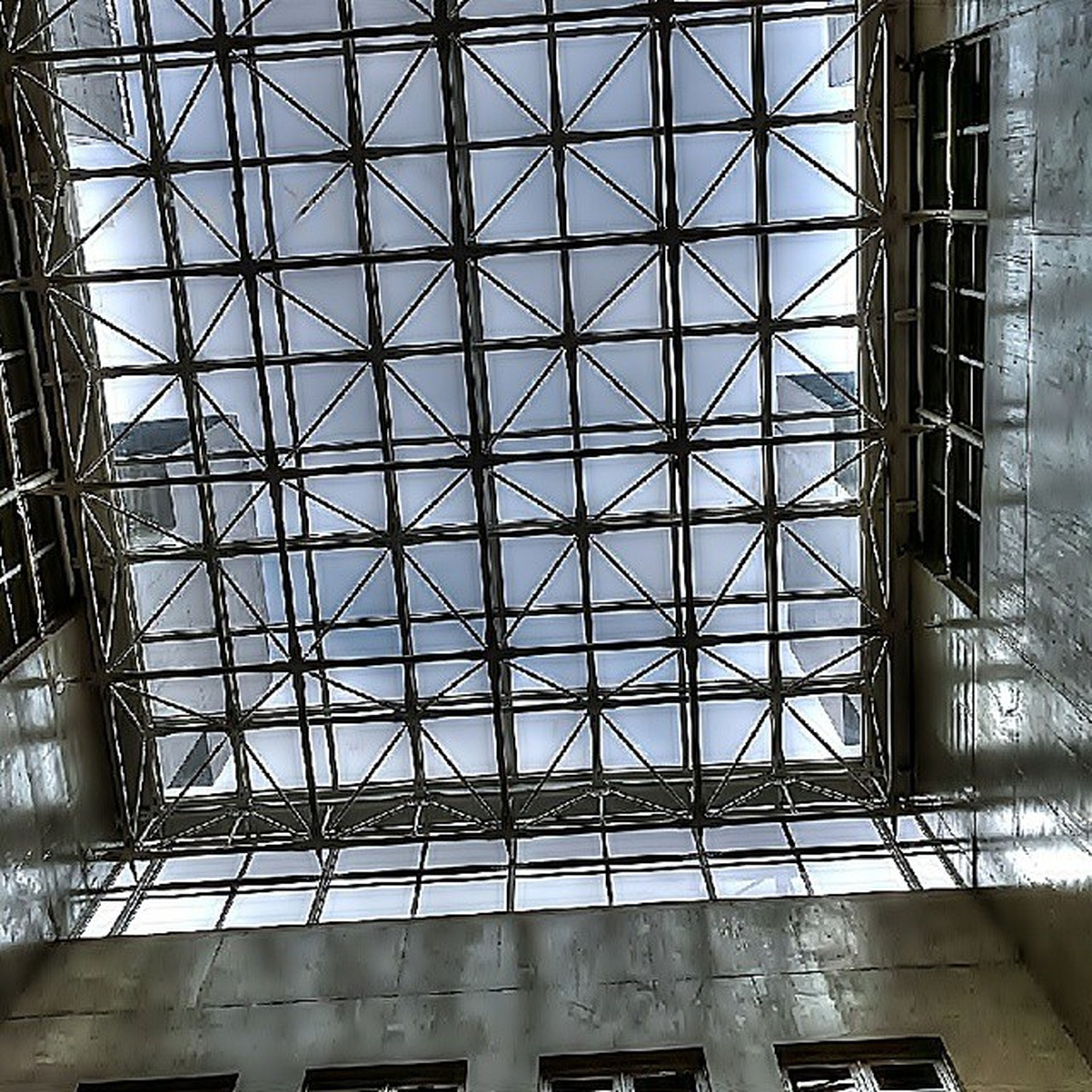architecture, built structure, low angle view, indoors, glass - material, architectural feature, ceiling, building exterior, pattern, design, window, modern, skylight, directly below, famous place, no people, building, day, geometric shape, sky