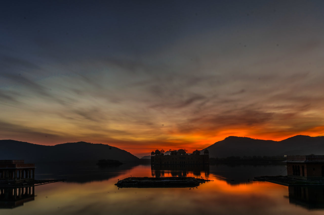 sunset, water, architecture, built structure, building exterior, sky, orange color, nature, reflection, outdoors, mountain, cloud - sky, beauty in nature, silhouette, no people, waterfront, scenics, travel destinations, city, day