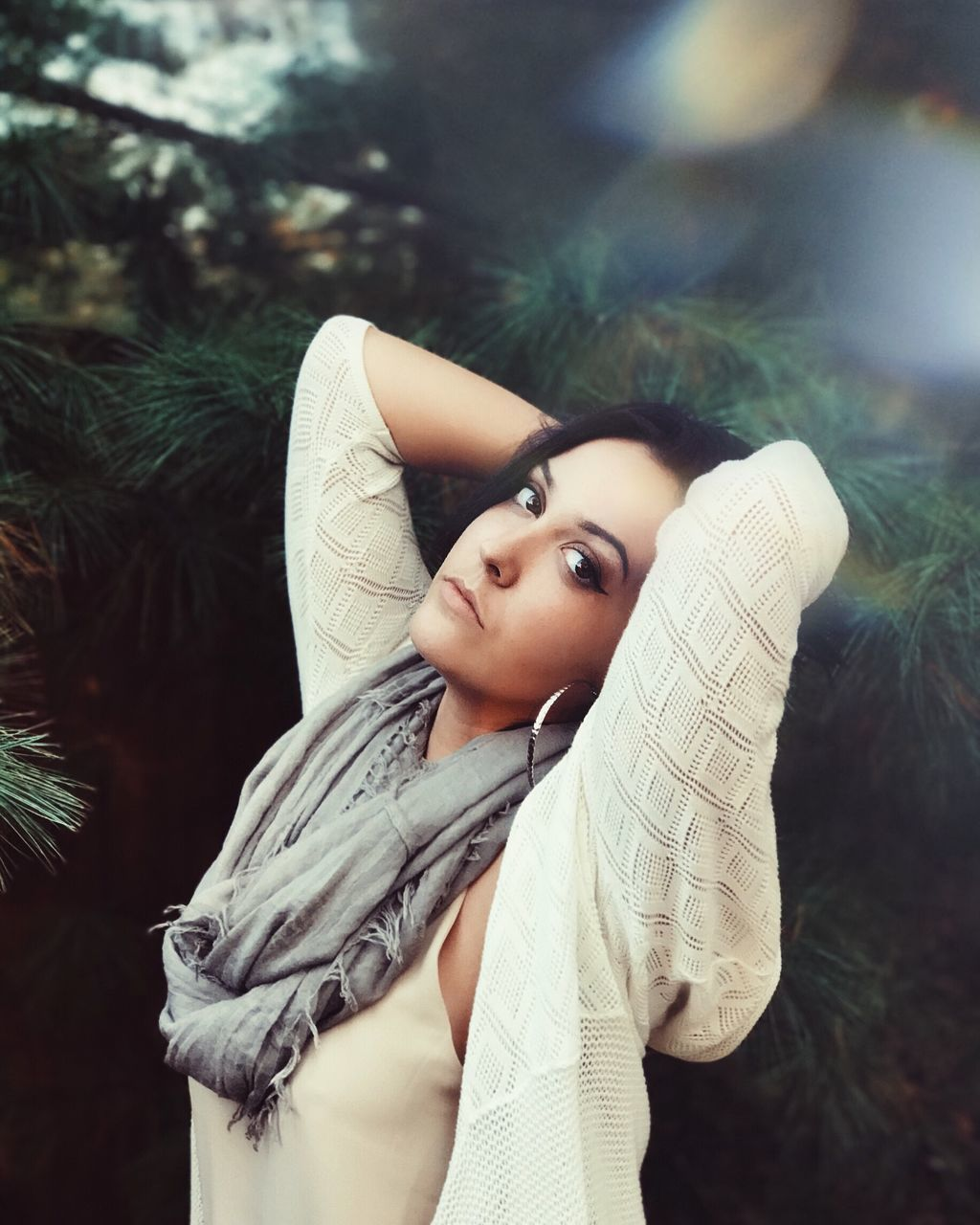 Portrait Of Young Woman With Hands Behind Head Against Tree