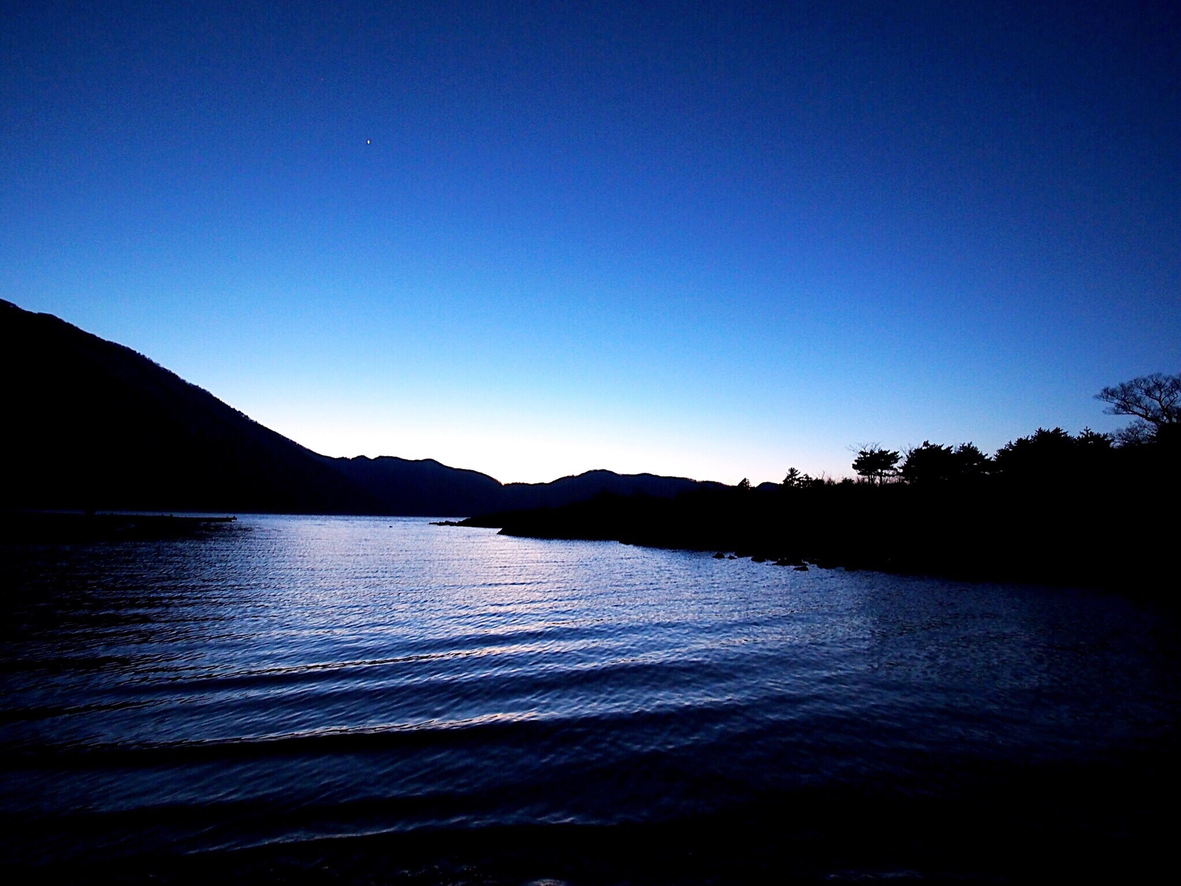 water, reflection, blue, silhouette, nature, tranquil scene, sky, tranquility, beauty in nature, scenics, clear sky, outdoors, no people, mountain, tree, day