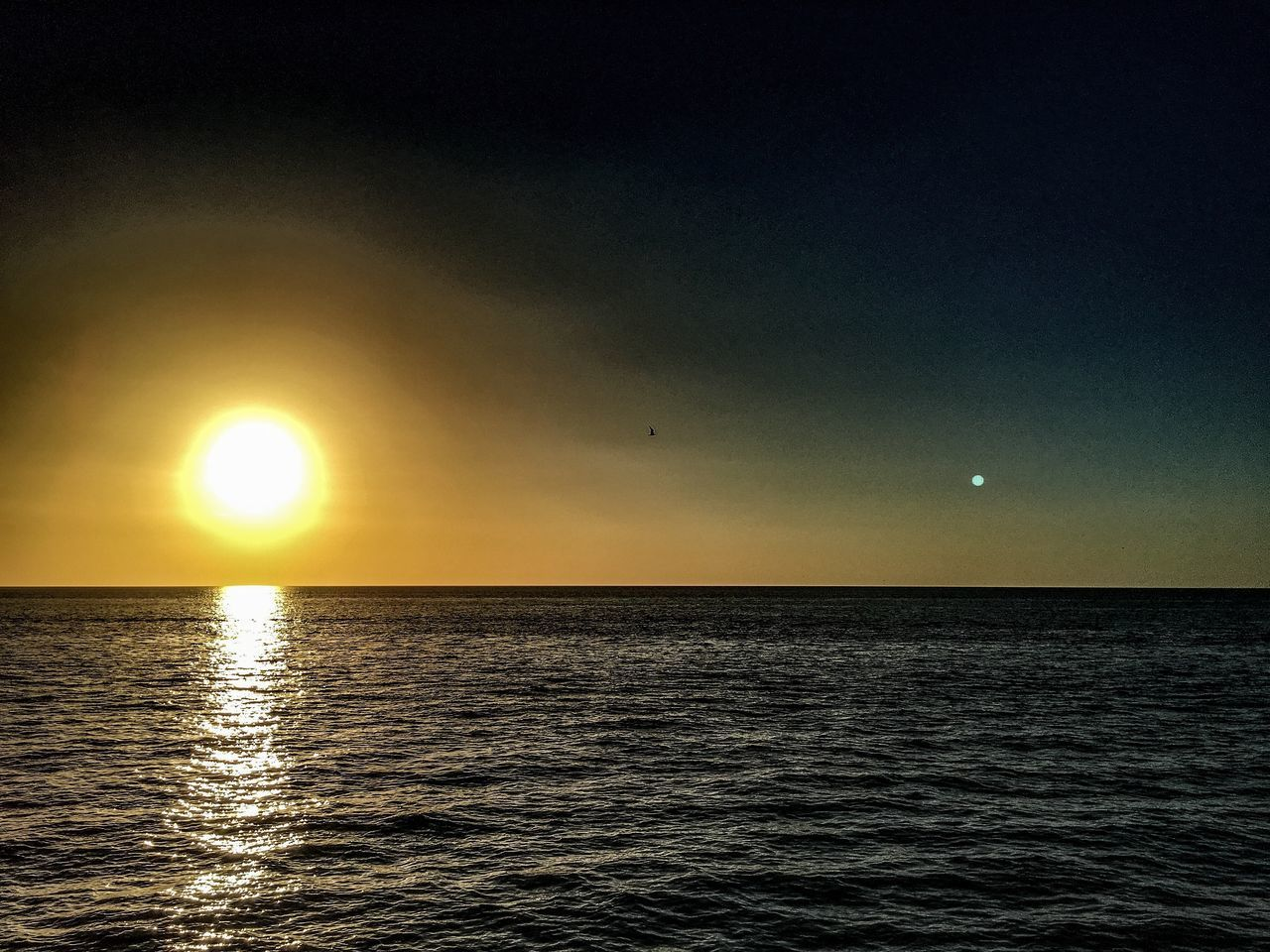 sea, beauty in nature, scenics, sunset, sun, tranquil scene, nature, horizon over water, water, tranquility, idyllic, waterfront, sky, outdoors, rippled, no people, reflection, moon, silhouette, yellow, clear sky, day