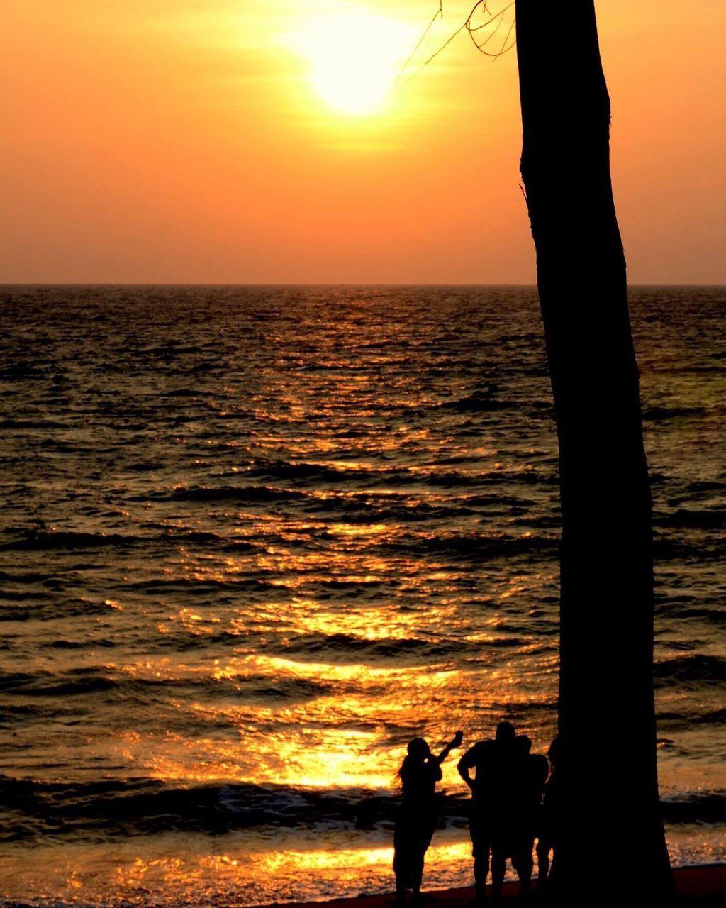 SILHOUETTE PEOPLE ENJOYING IN SEA AGAINST SUNSET SKY