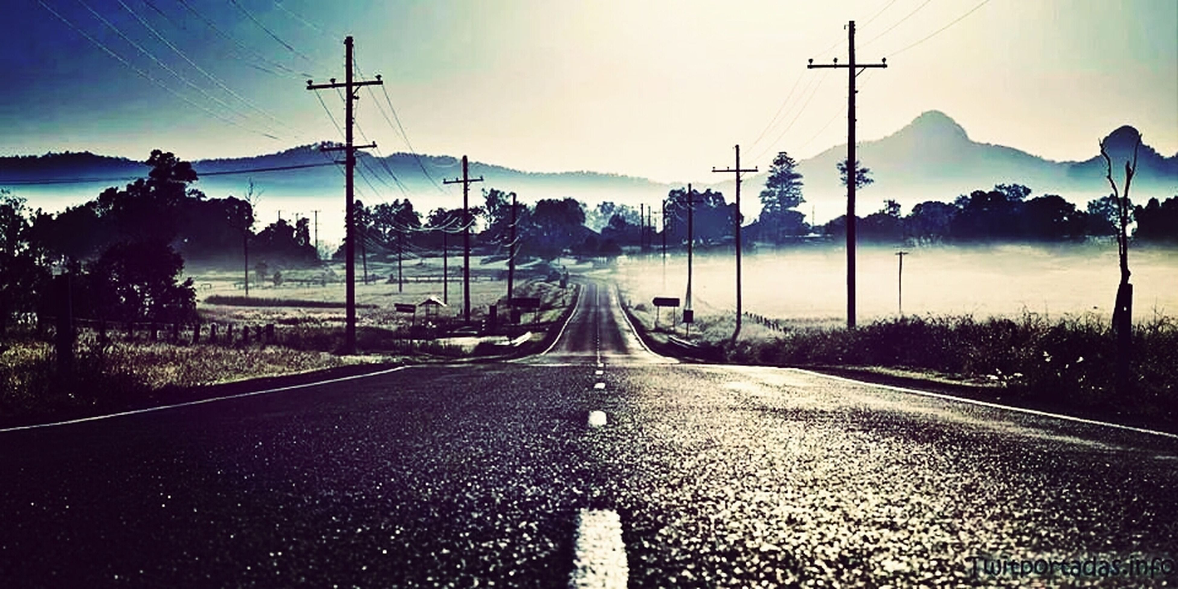 transportation, electricity pylon, the way forward, road, power line, diminishing perspective, mountain, electricity, sky, vanishing point, country road, power supply, landscape, cable, empty road, road marking, fuel and power generation, tree, mountain range, clear sky