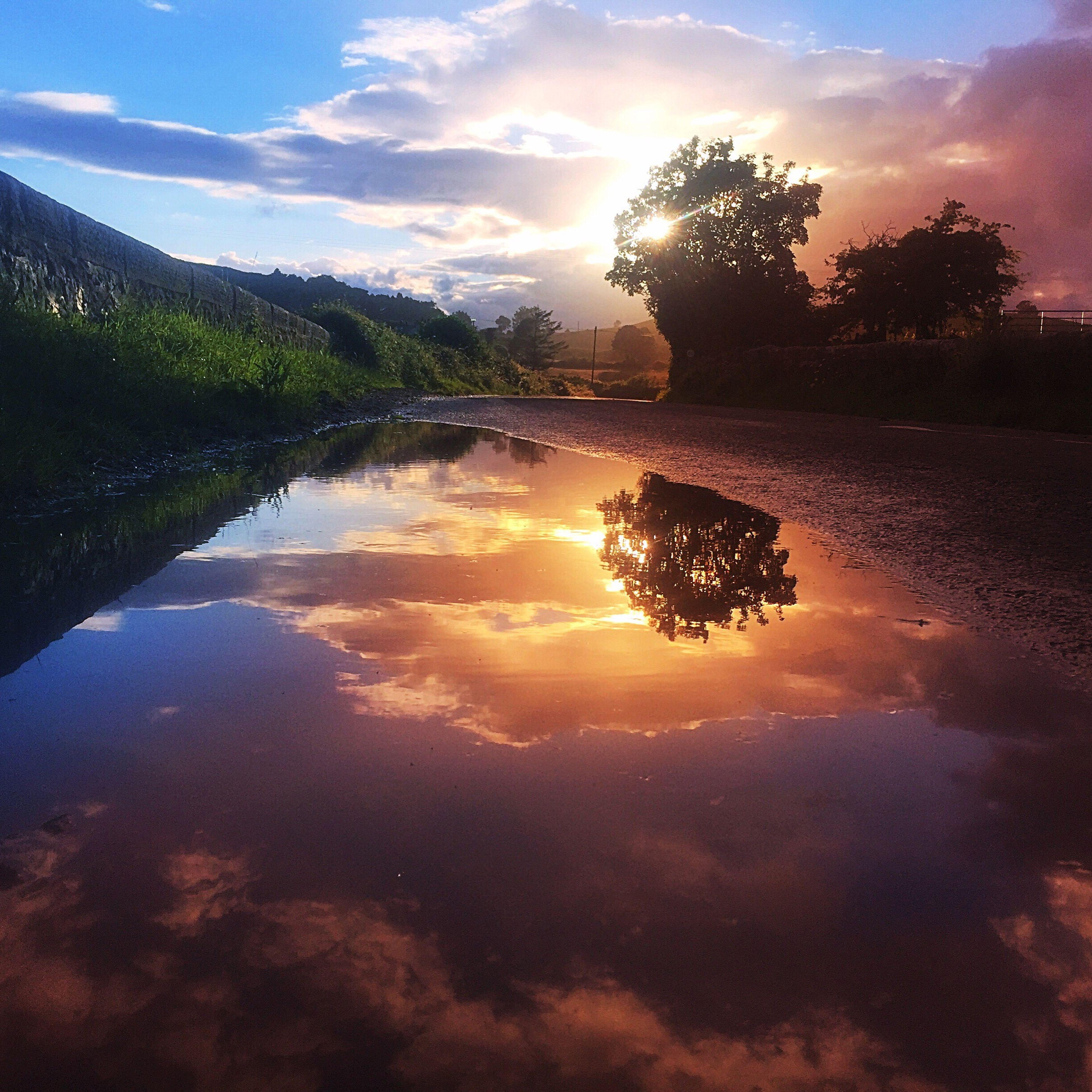 sunset, reflection, sky, water, nature, cloud - sky, tree, beauty in nature, sun, scenics, sunlight, idyllic, vacations, lake, sunbeam, silhouette, outdoors, landscape, reflection lake, no people, day